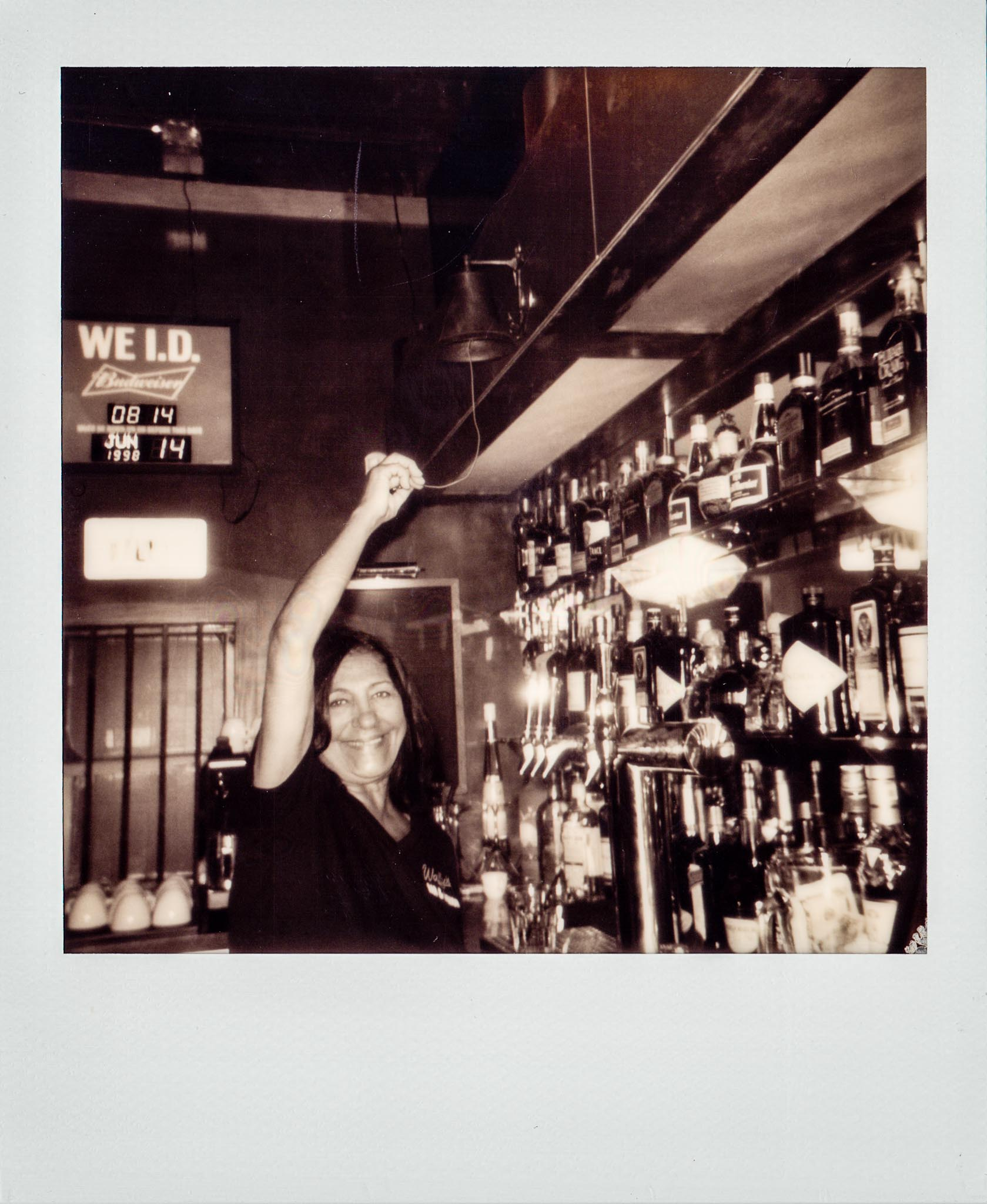 Cindy the bartender ringing the bell at Wallys Mills Avenue Liquors