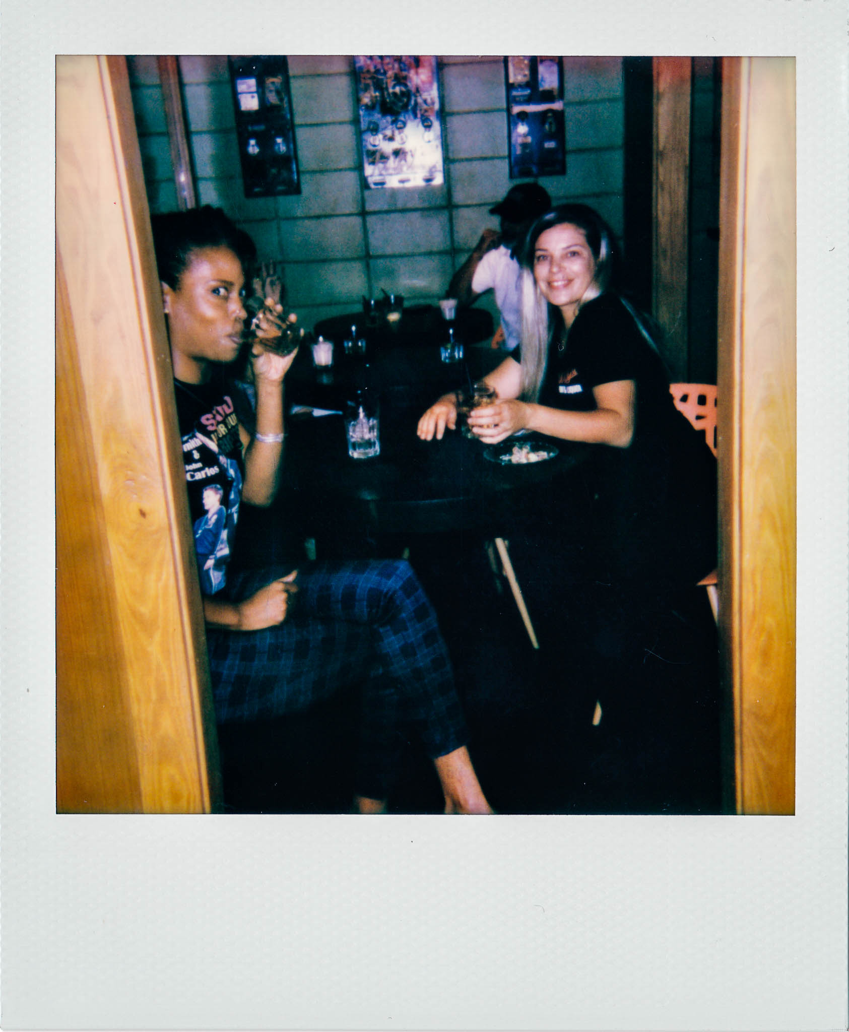 Two woman sitting, smiling, and drinking, at Wallys Mills Avenue Liquors