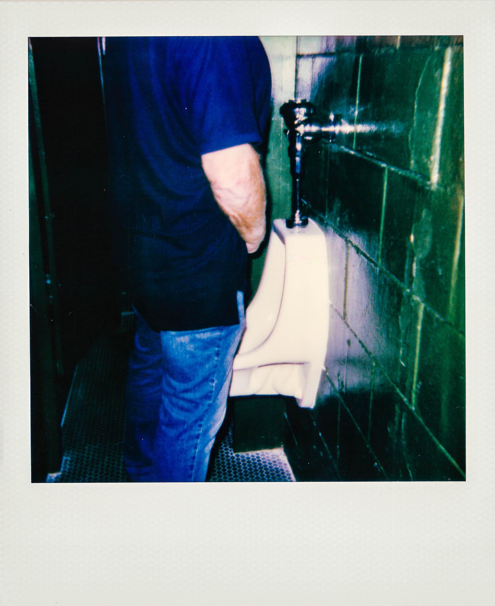 Man peeing in urinal at Wallys Mills Avenue Liquors