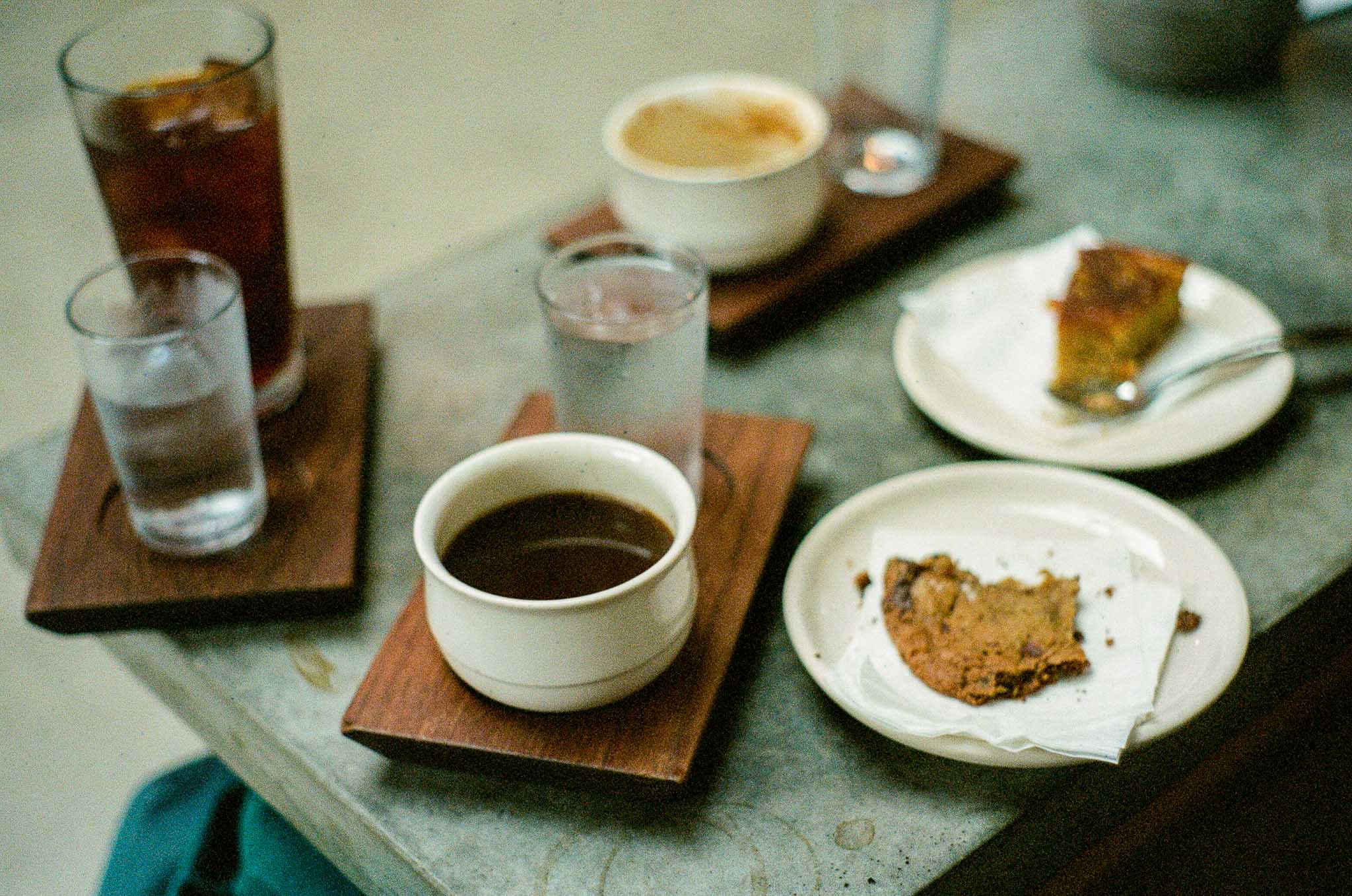 A table filled with wooden platters and plates of coffee and pastries at Sey Coffee in Brooklyn New York