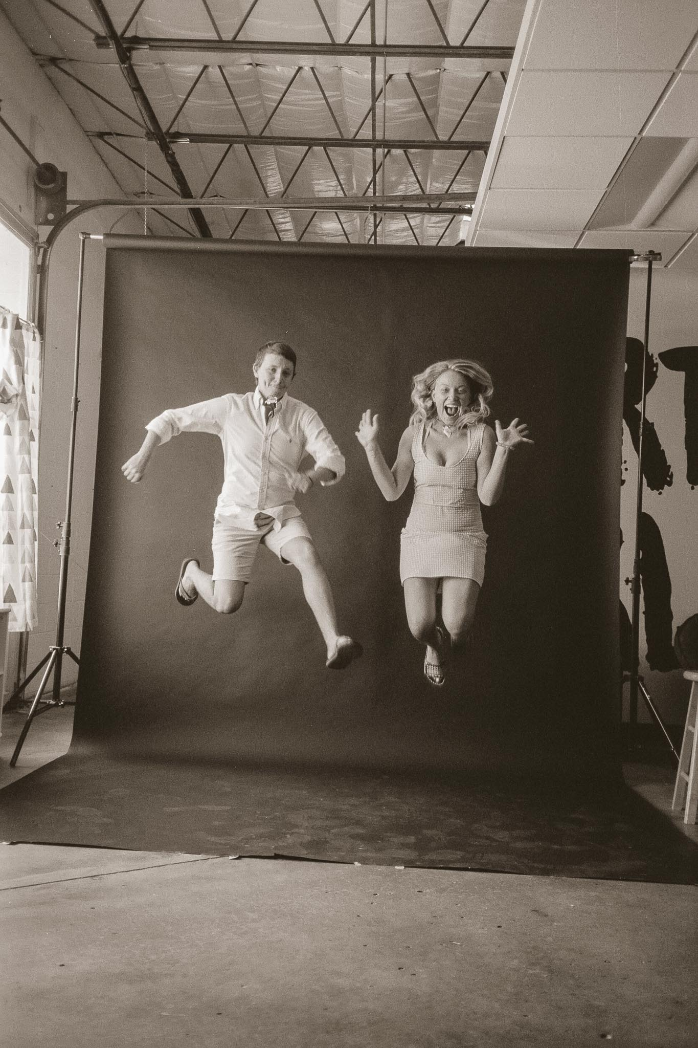 Guy and girl jumping in front of a studio backdrop