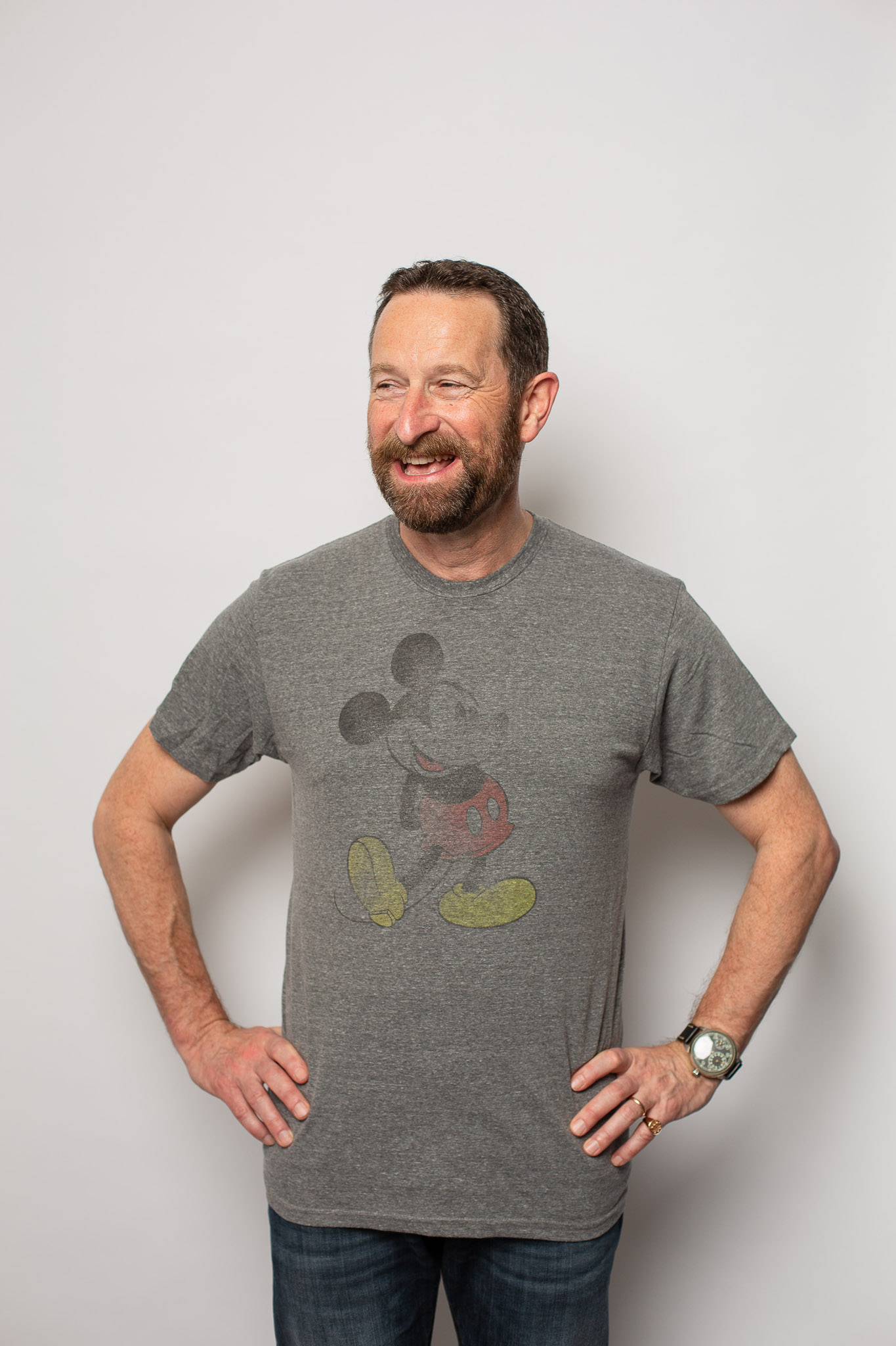 Duncan Wardle on a white backdrop with a grey Mickey Mouse T Shirt.