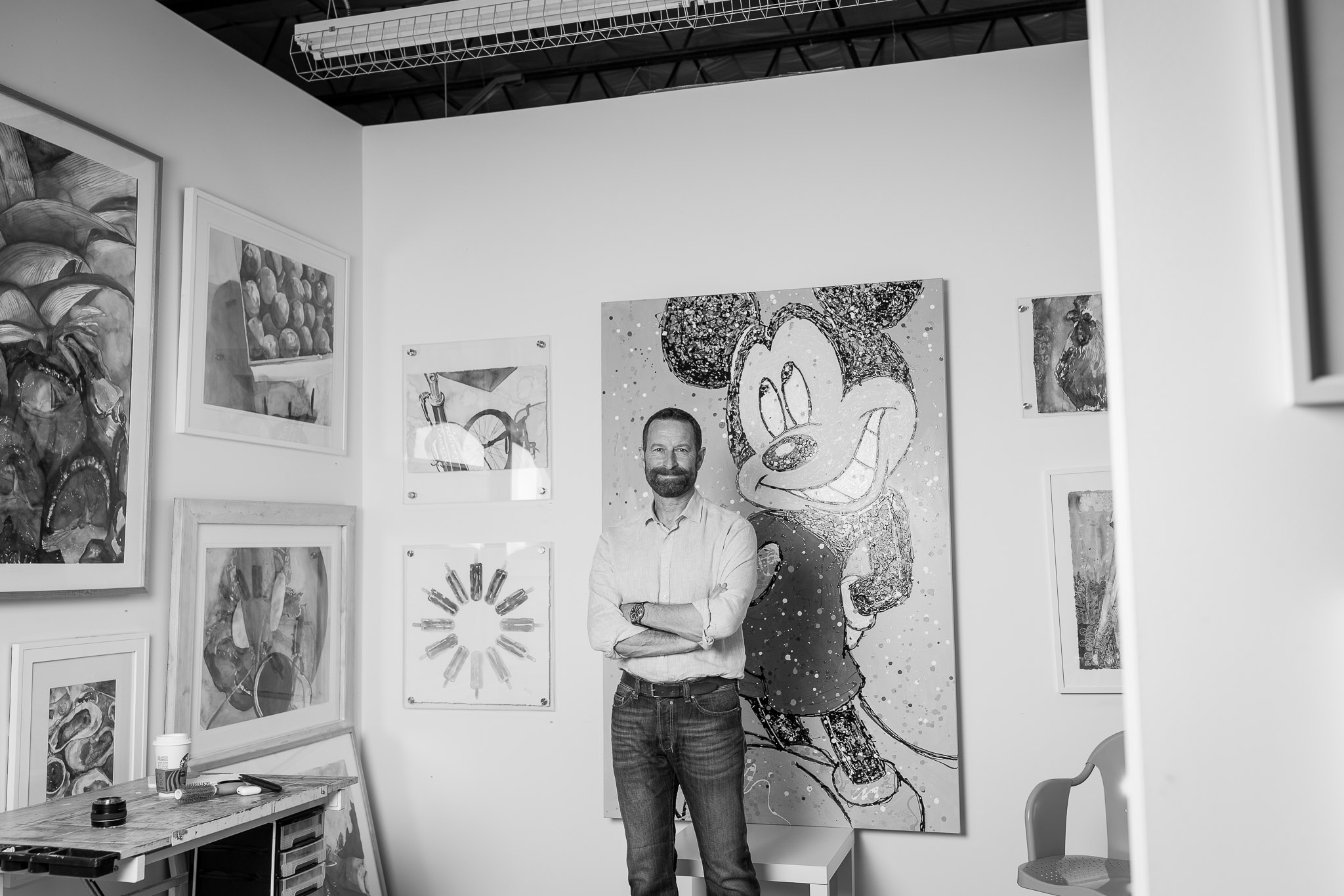Duncan Wardle standing in front of his Mickey Painting in a room full of colorful art.