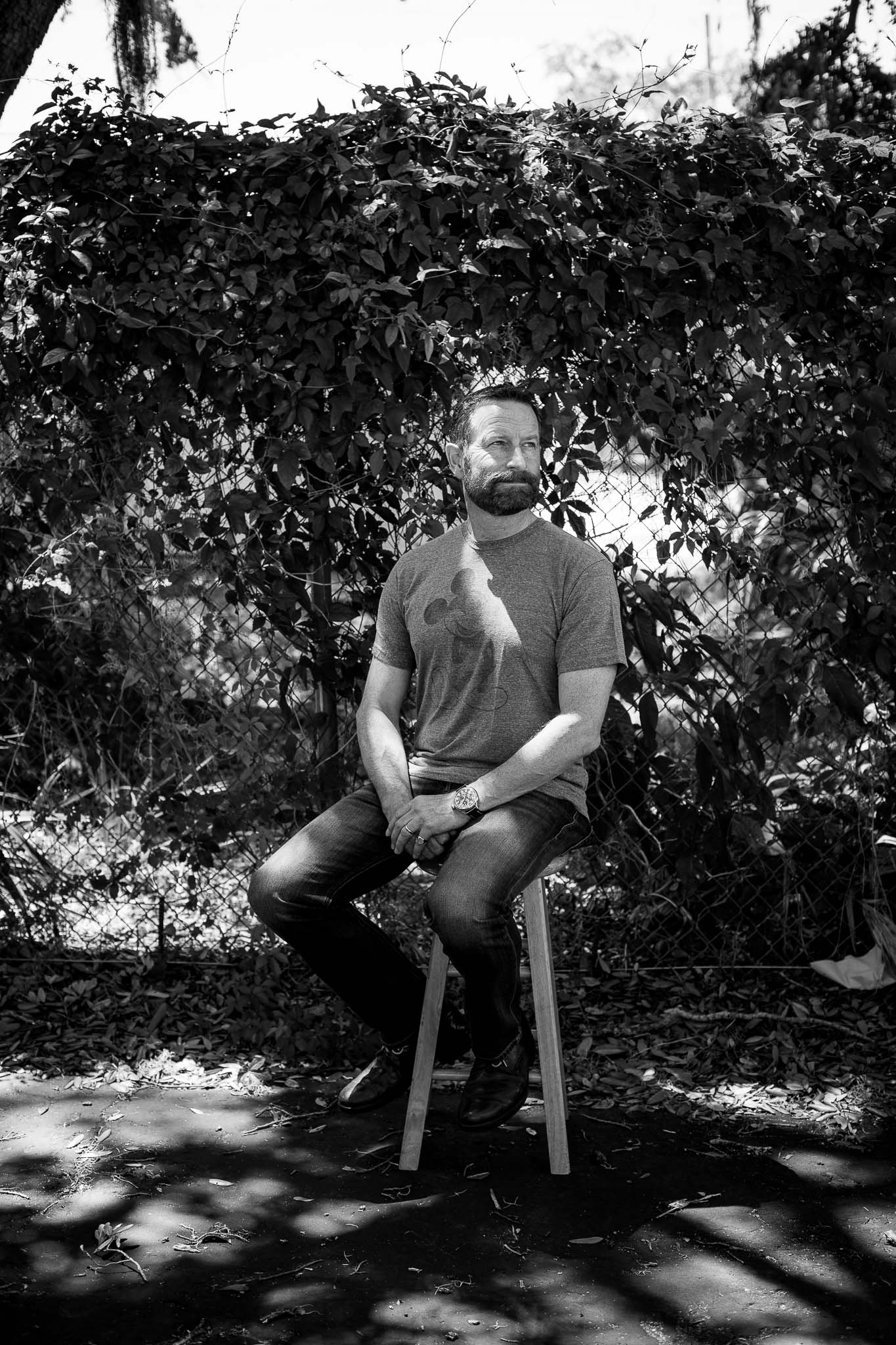 Black and white image of Duncan Wardle sitting outside on a stool in speckled light.
