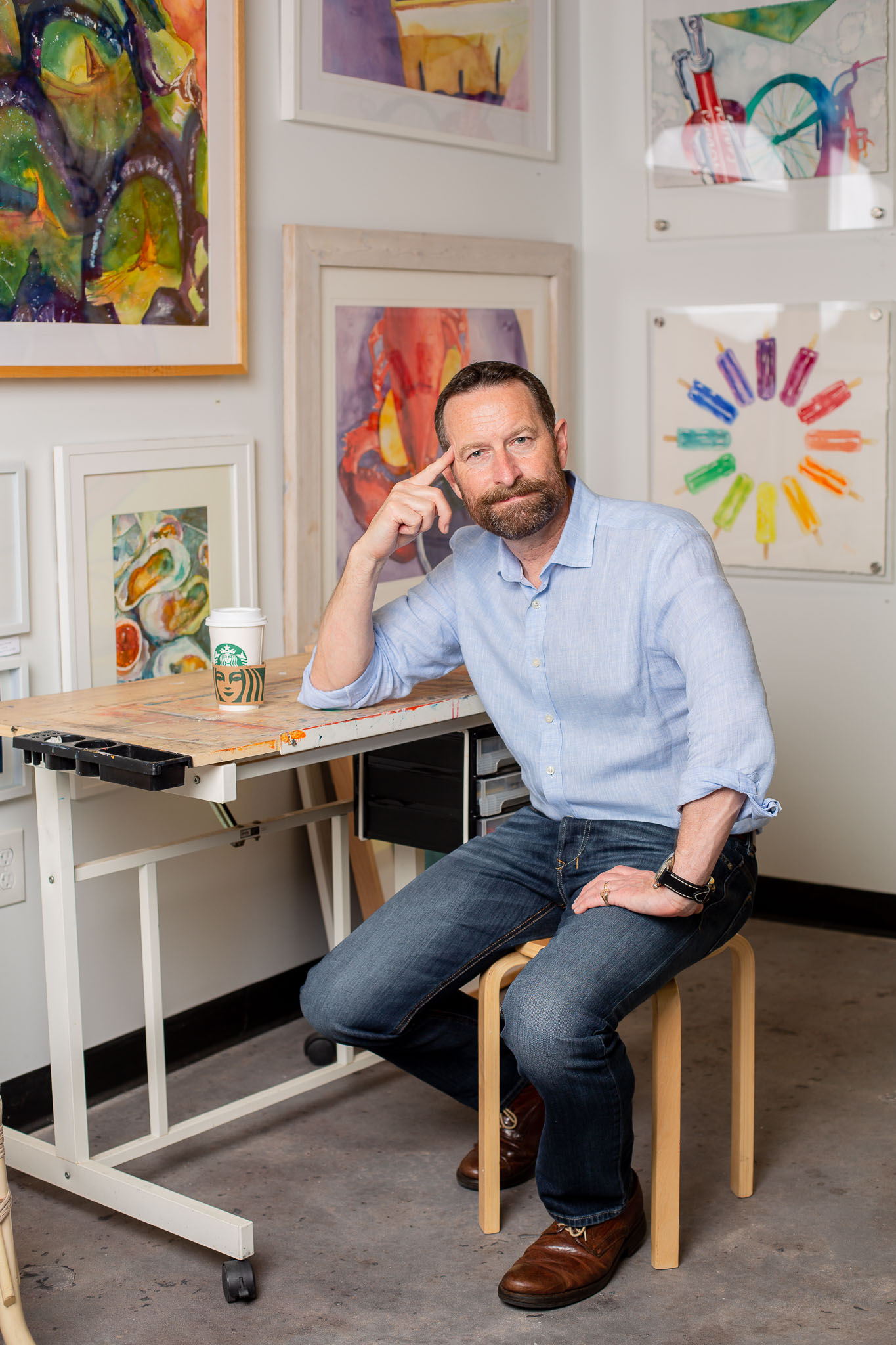 Duncan Wardle sitting in an art studio next to a starbucks cup.