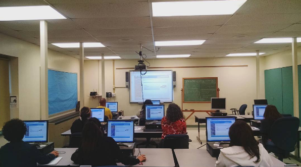 An ESL class  gaining computers skills while working on English   grammar  exercises.