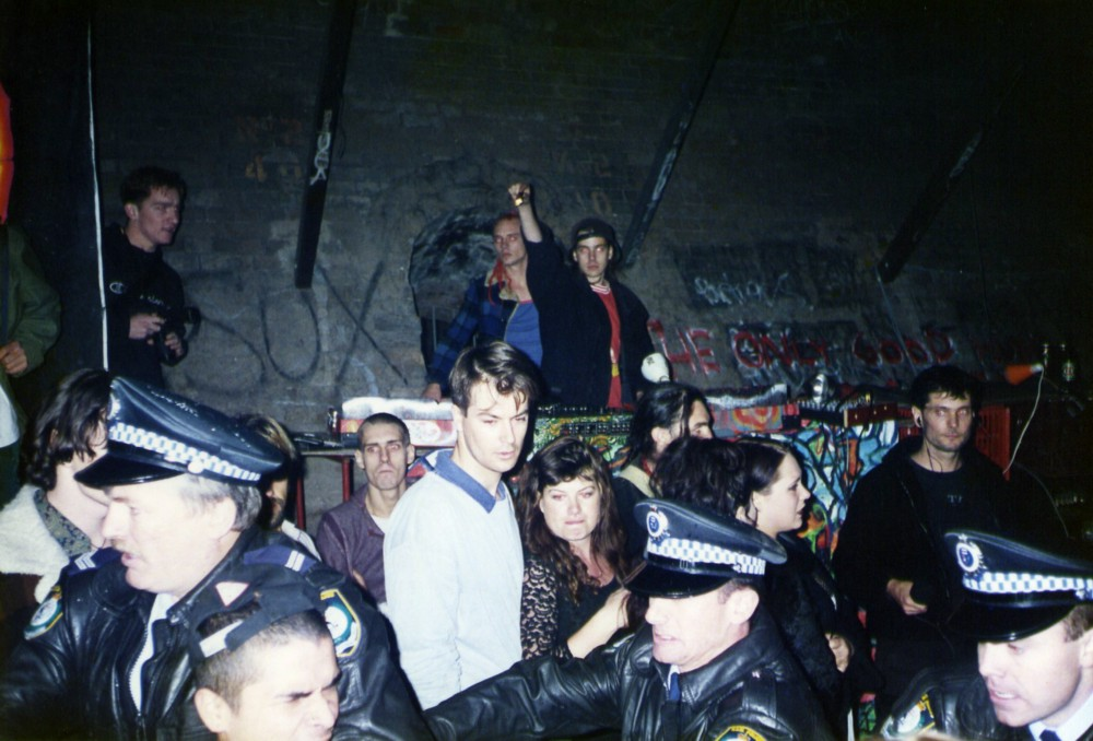A 1995 rave in Australia being broken up by police. Recreational MDMA use spread globally with rave party culture. (Wikimedia)