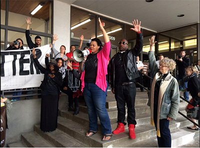 Lena Gardner (pink sweater), UU justice leader and member of First Universalist Church - Minneapolis, Pastor Danny Givens, and Rev. Ruth Mackenzie (Associate Minister at First Universalist) lead the crowd in a Black Lives Matter solidarity action for the #MOA36 at the Hennepin Co. Courthouse, May 1, 2015. (Photo: Ashley Horan)