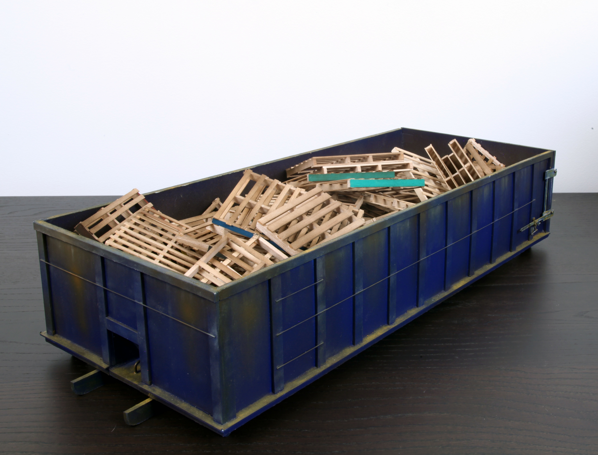 Blue 30 yard Dumpster with 55 pallets