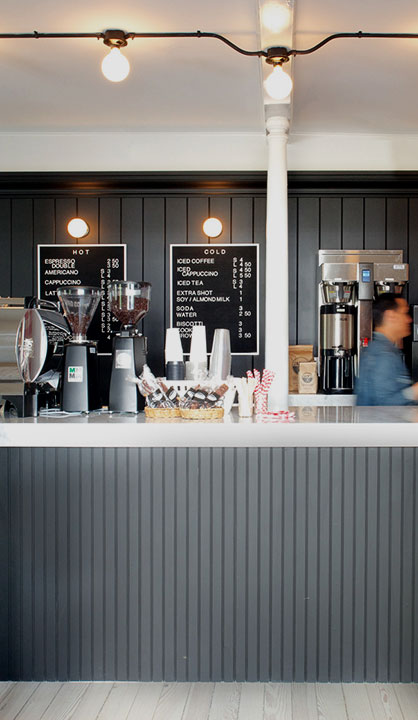 grey coffee counter with man, cups, light