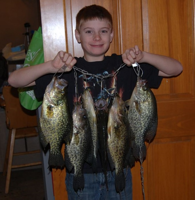 This boy is holding a stringer of fish he caught  while at Whitetail Lodge.