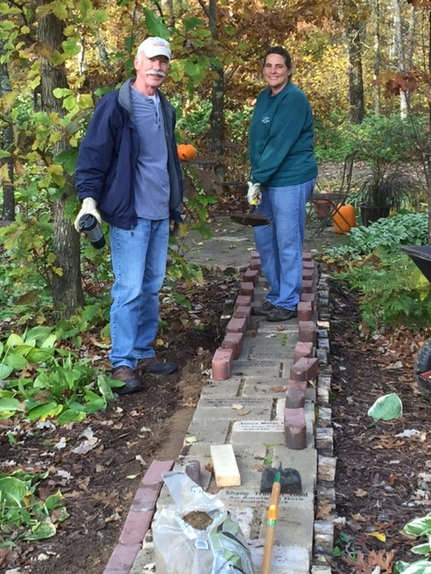Paul and Amy M working on placing new edgers along our Pathway of Hope Gardens walkway.