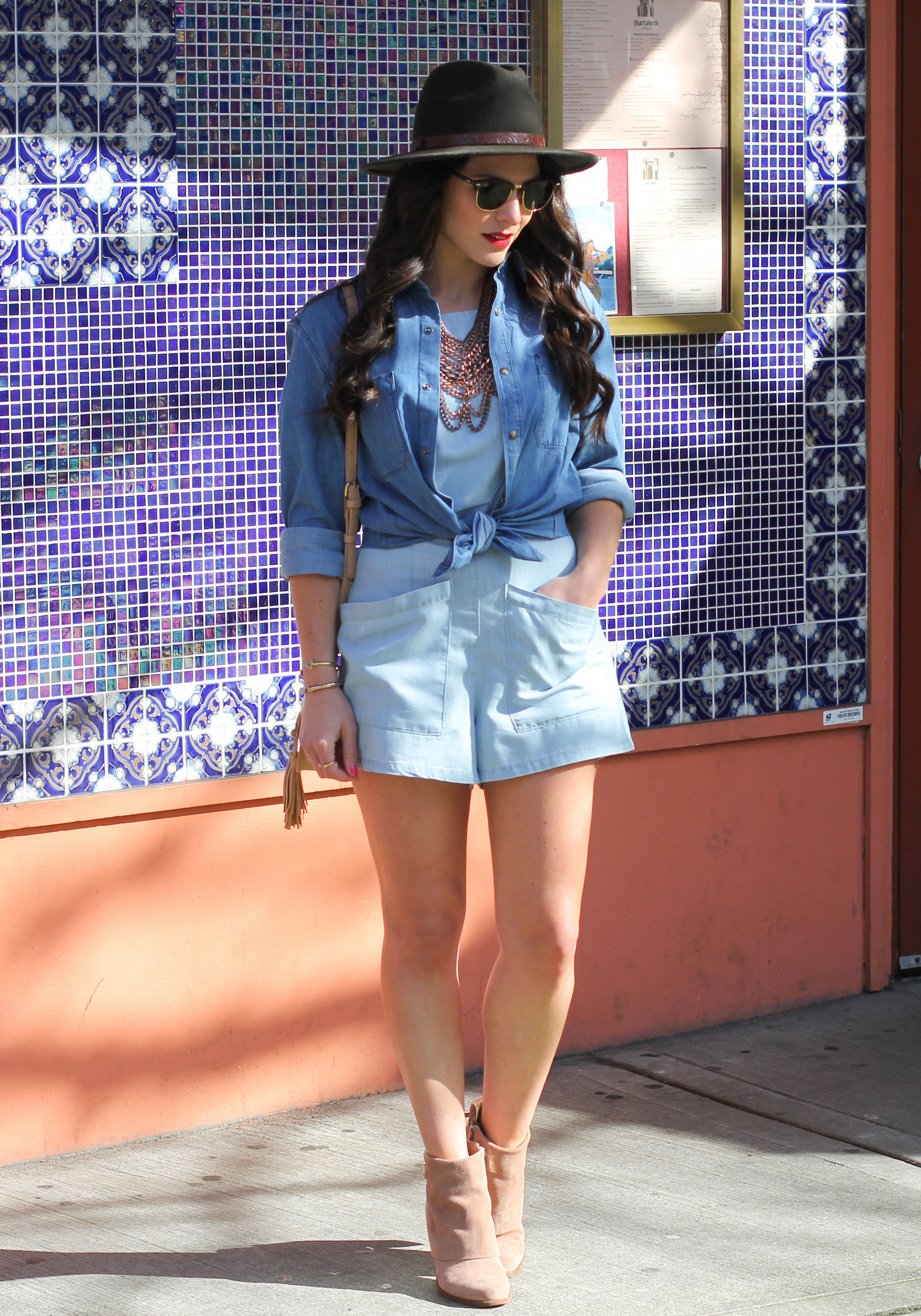 Spring Outfit, Denim Boyfriend Shirt, BDG High Neck Chambray Romper, Baublebar Courtney Bib Necklace, Green Fedora, Tan Suede Booties, & Tan Crossbody with Tassels
