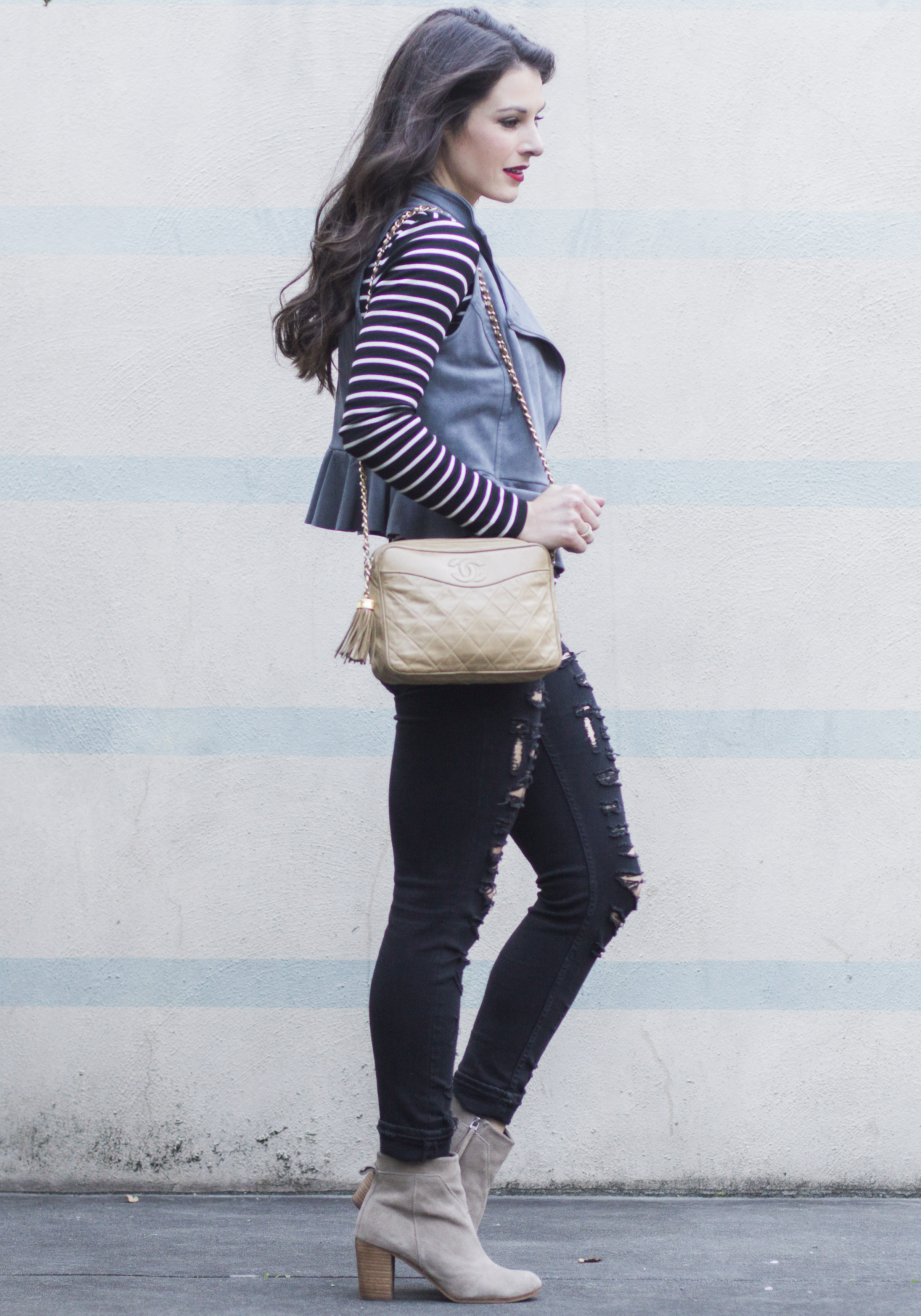 Mixing edgy and feminine pieces to create cute fall outfits: LC Lauren Conrad ruffle peplum vest, Blank NYC ripped skinny jeans, Long sleeve lace up top, Toms Lunata booties, and vintage Chanel handbag.