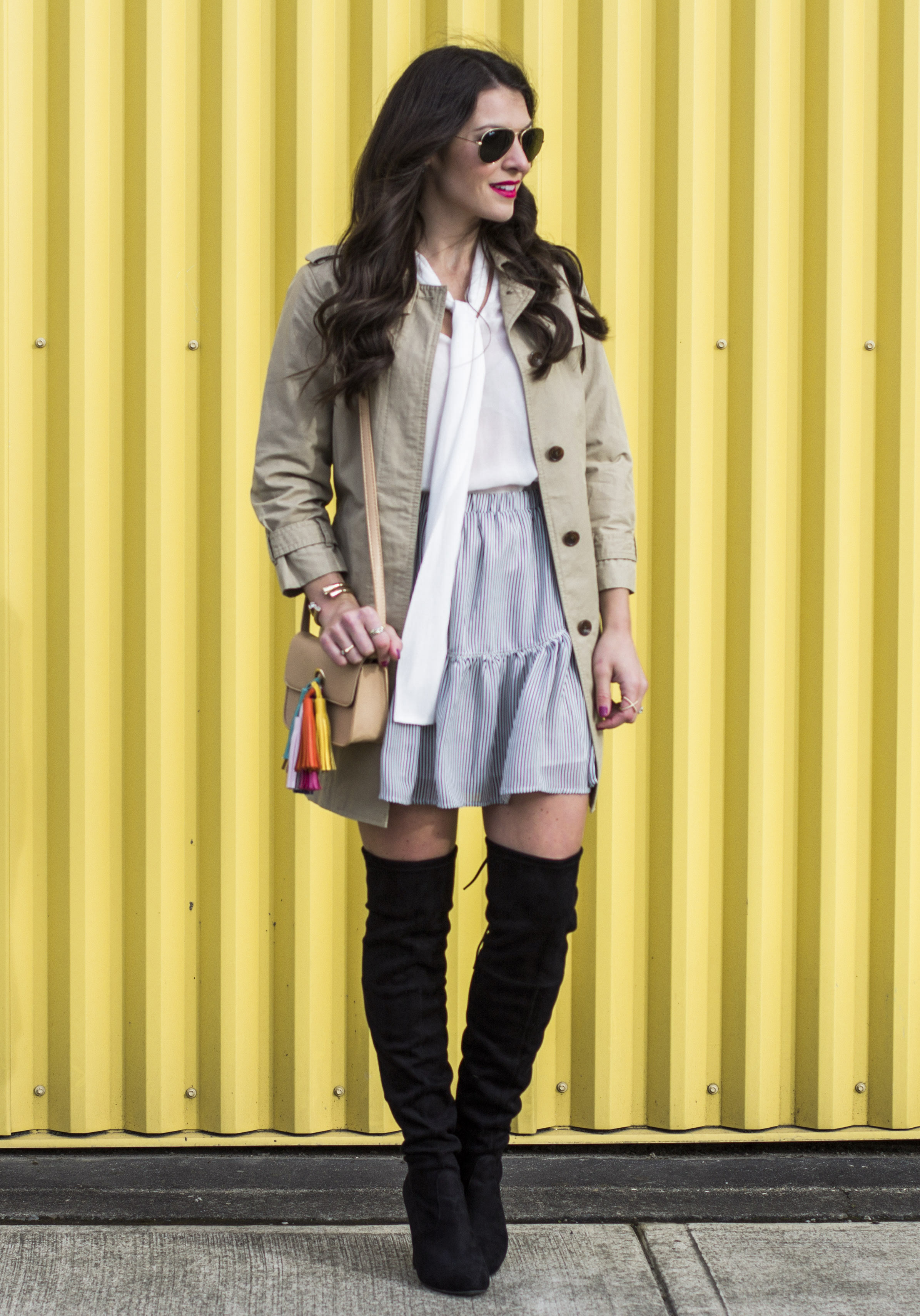 Cute fall outfits with otk boots, over the knee boot outfit ideas, Ruffle hem skirt with bow blouse, trench coat, and Steve Madden Gorgeous over the knee boots.