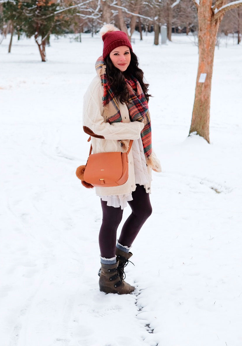 Cute snow day outfit, Sorel Joan of Arctic Wedge Boots, Cable knit cardigan, Pom pom beanie, Mark & Graham Daily Saddle Bag, Spanx faux leather leggings, and a plaid blanket scarf.
