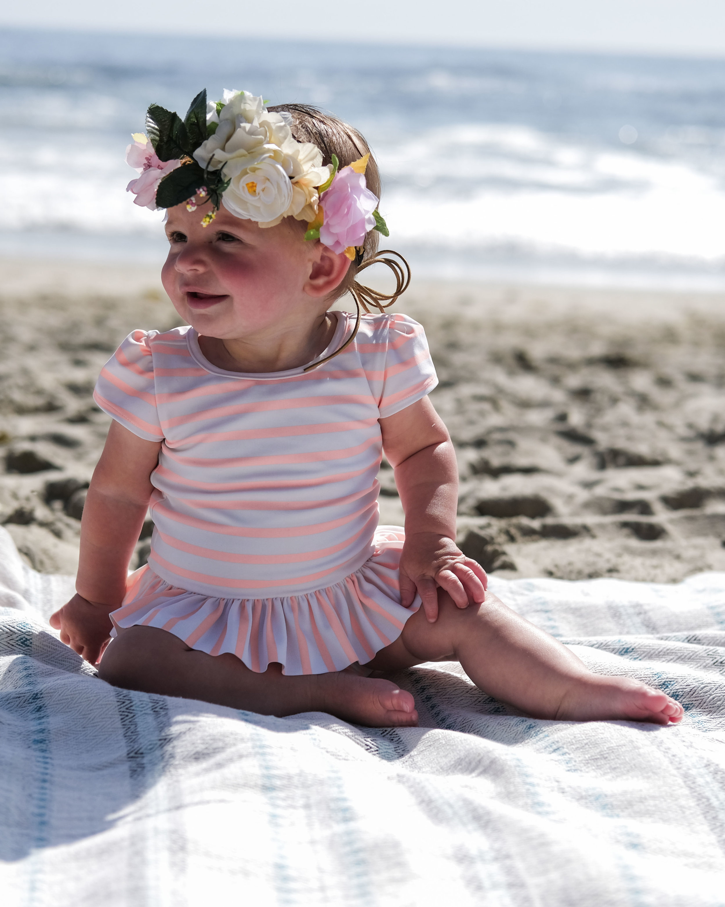 Cute baby portrait at the beach.  One piece swimsuit with flower crown and striped towel.