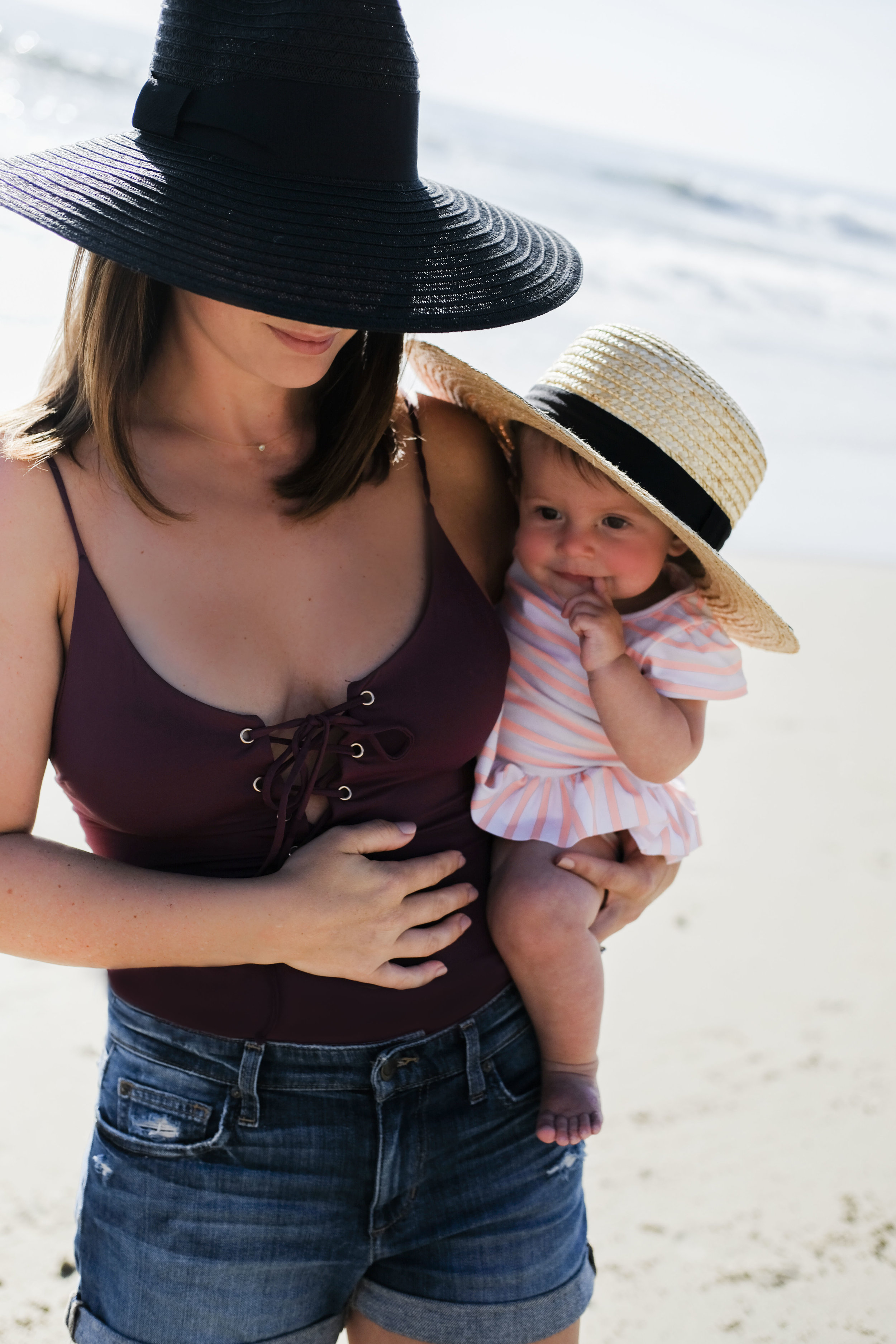 Family portrait on the beach, mom and baby in swimsuits and hats.  Beach family photos.