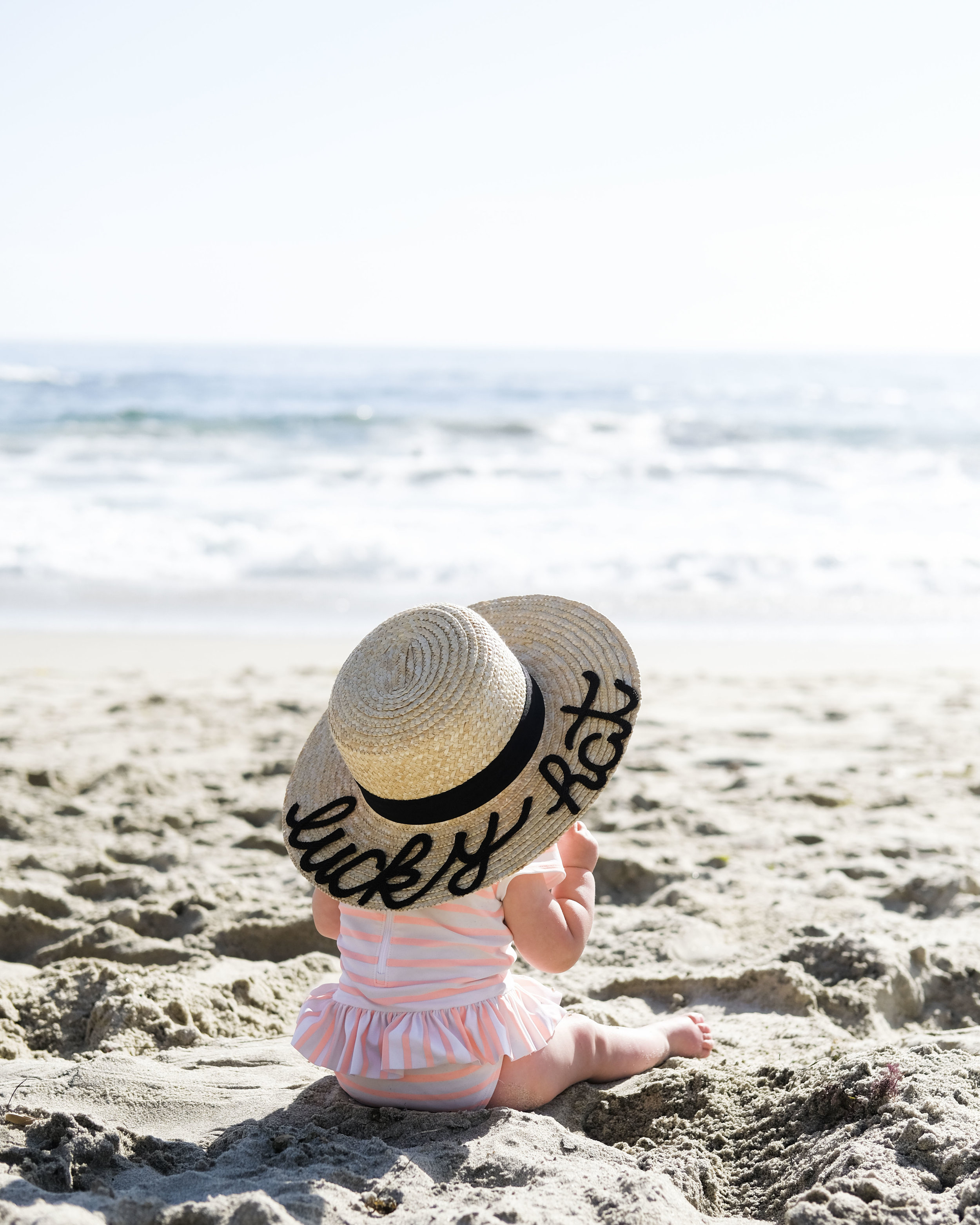 Baby portrait on the beach.  Casual family photos in swimsuits. DIY Eugenia Kim hat for baby.