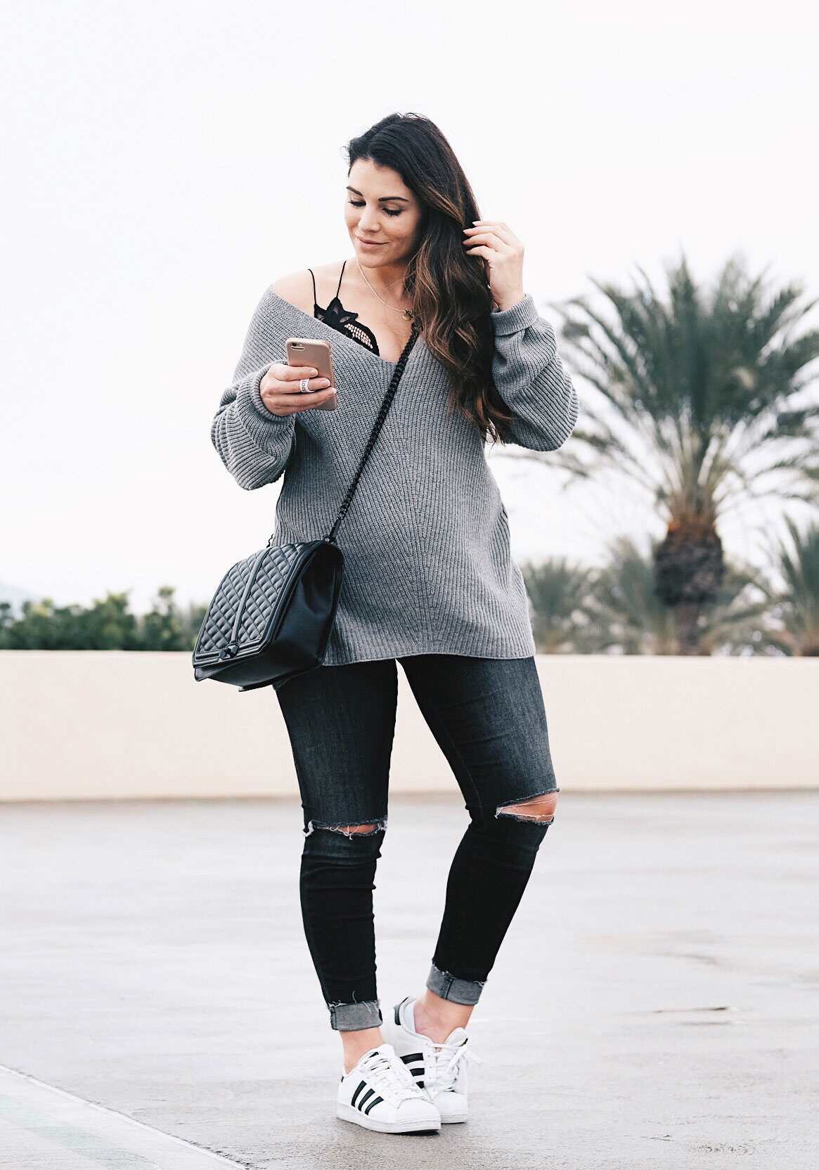 Second trimester maternity outfit.  V-neck sweater with Free People Adella bralette, gray distressed maternity jeans, and Adidas sneakers.