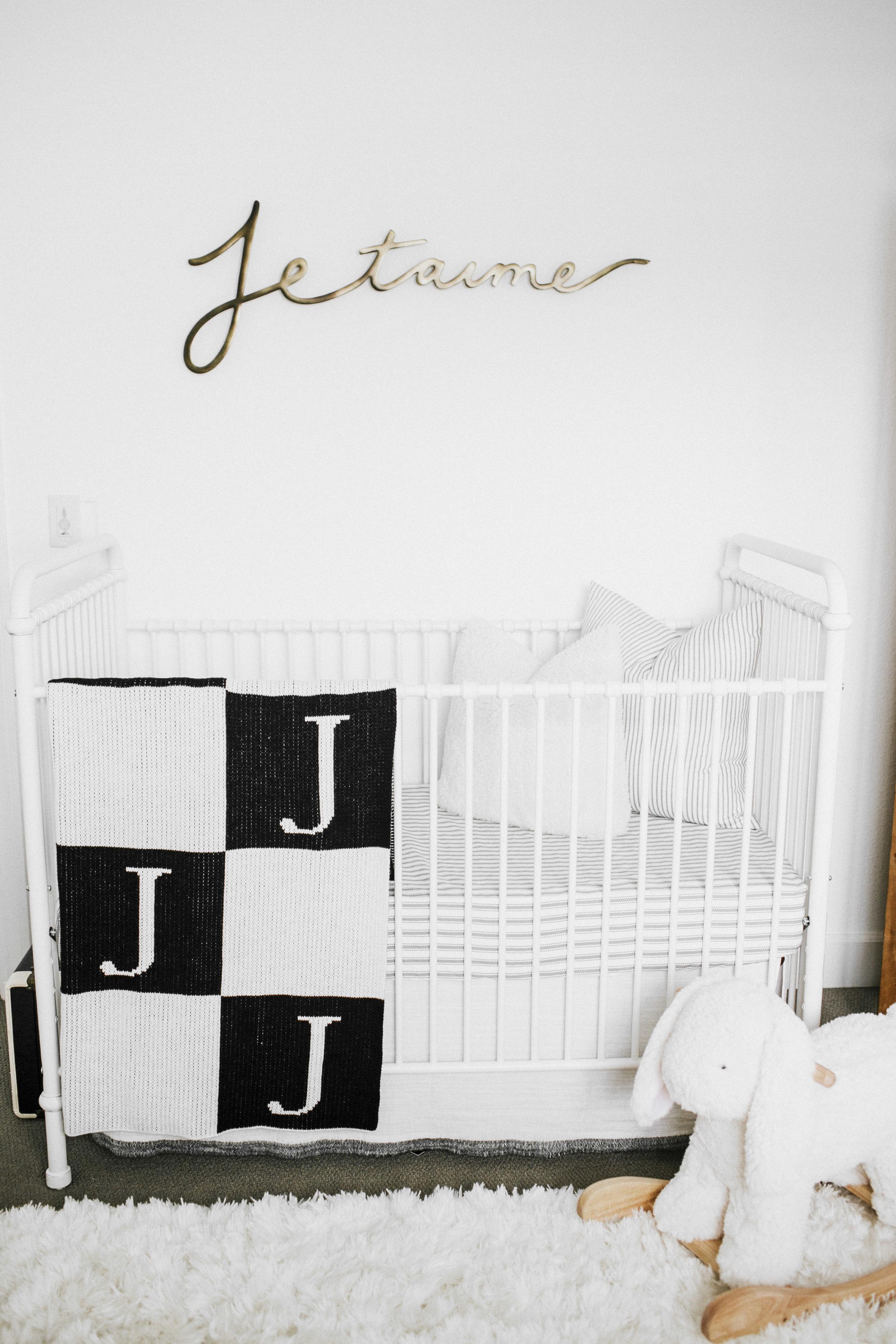Neutral nursery.  Black and white nursery.  Pottery Barn Kids sherpa bunny plush rocker. White wrought iron crib.