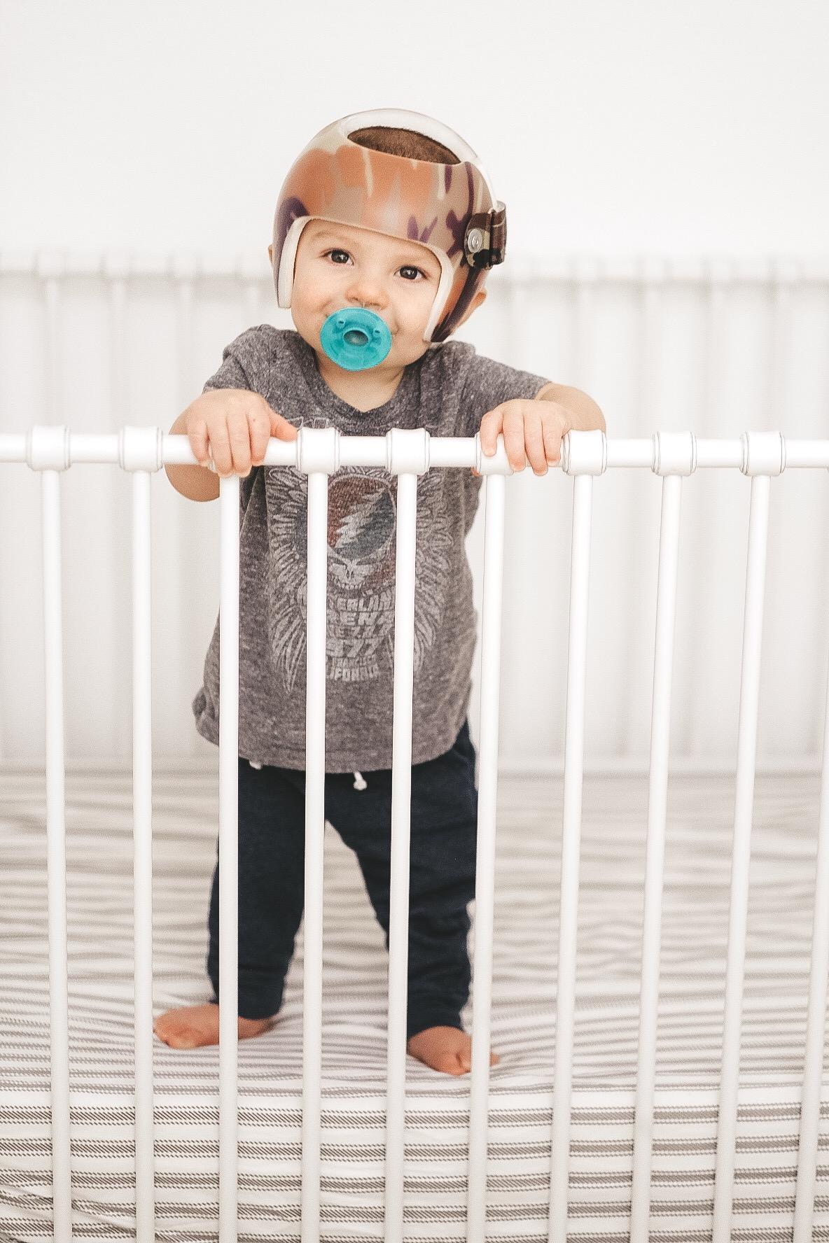 Jett Jones 10 mont update.  Cute white crib.  Black and white stripe crib sheet. Helmet treatment for Plagiocephaly.