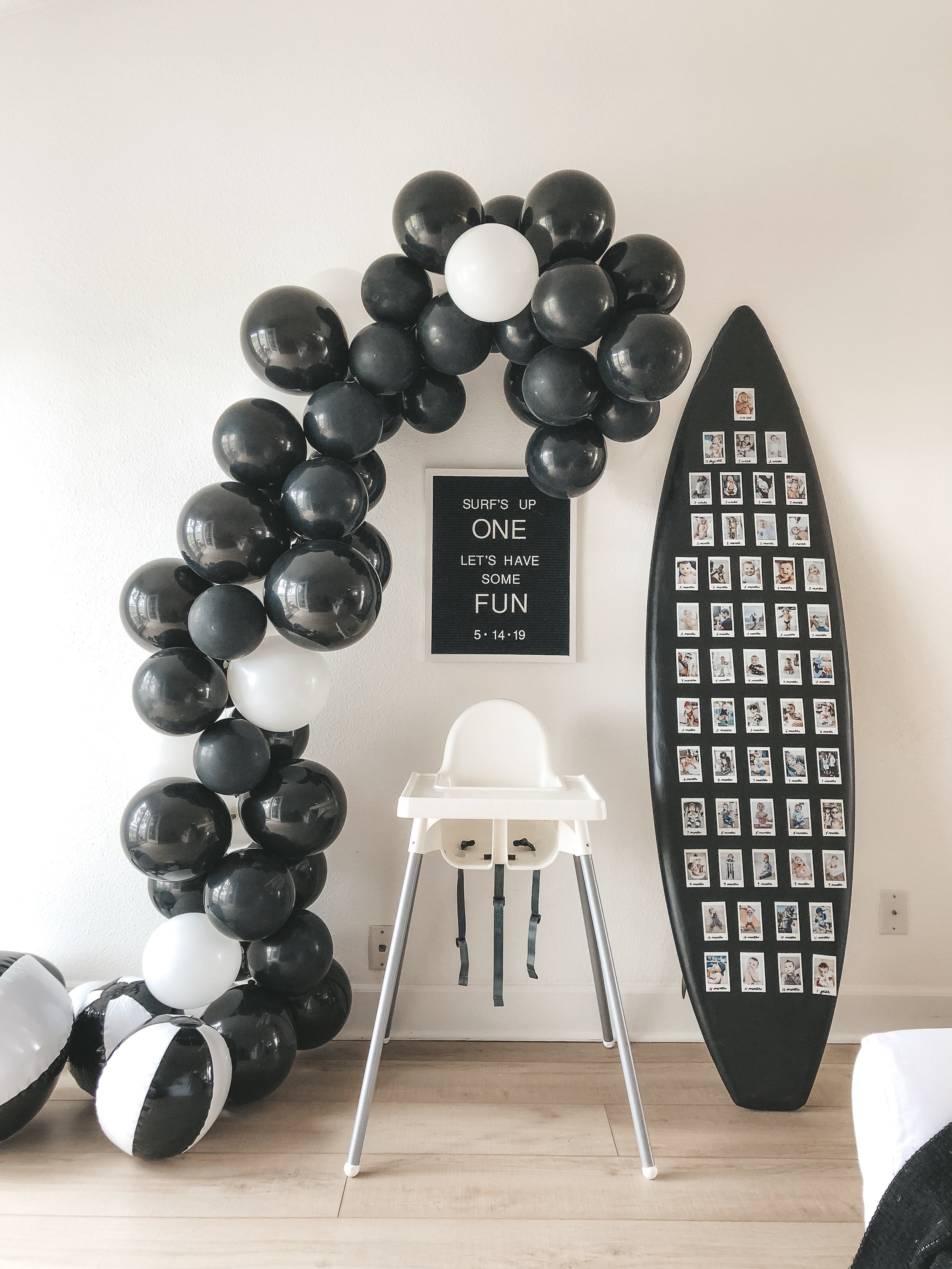 DIY BALLOON ARCH TUTORIAL TIPS TRICKS. How to make a balloon arch at home.  Inexpensive balloon arch party decor.  Surf theme first birthday party.  Surfboard with Polaroid photos of first year.  Beach ball balloon arch.