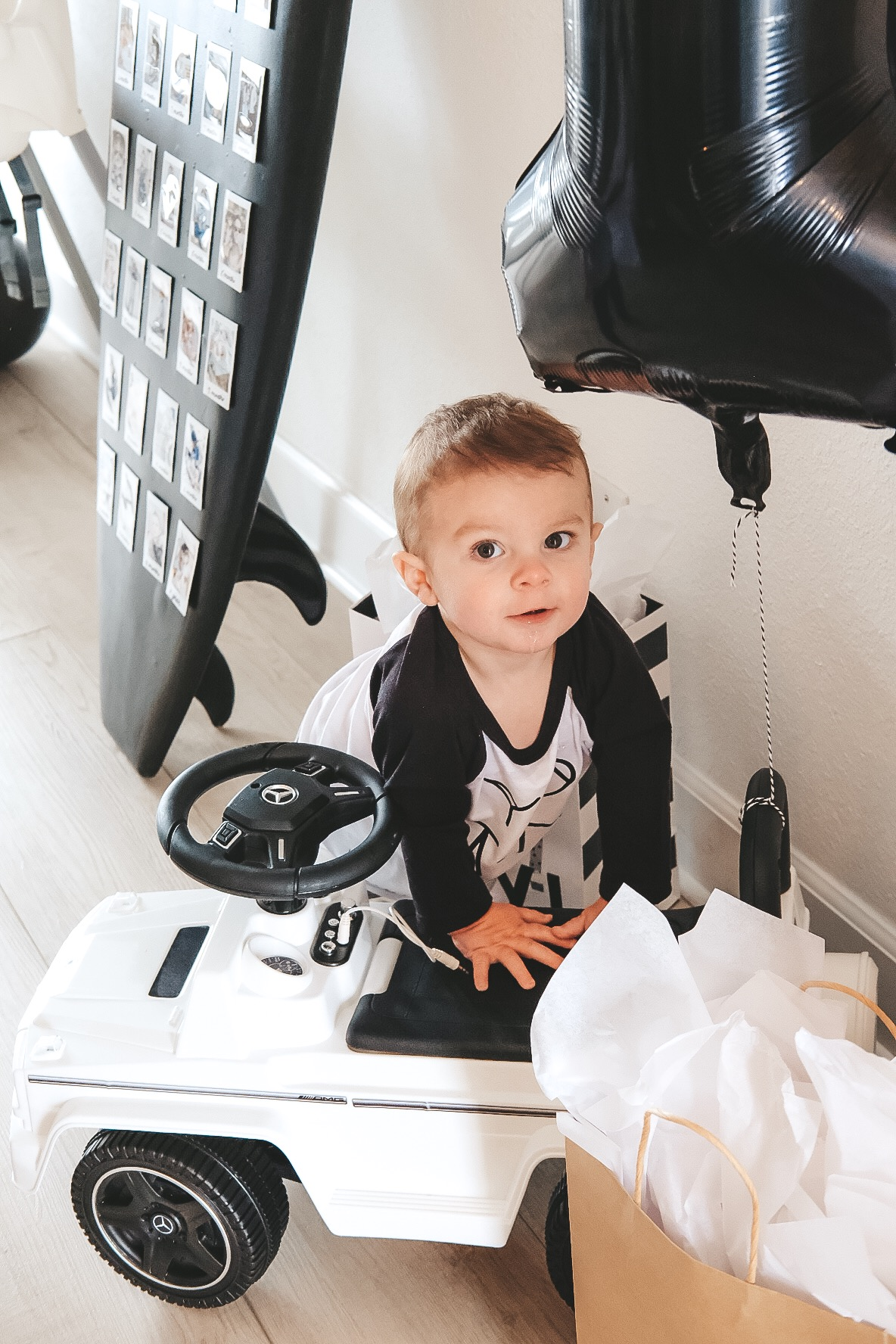 Modern surfer theme birthday party.  Black and white birthday party.  Baby boy frist birthday party. White G Wagon ride along car for 1 year old birthday gift.