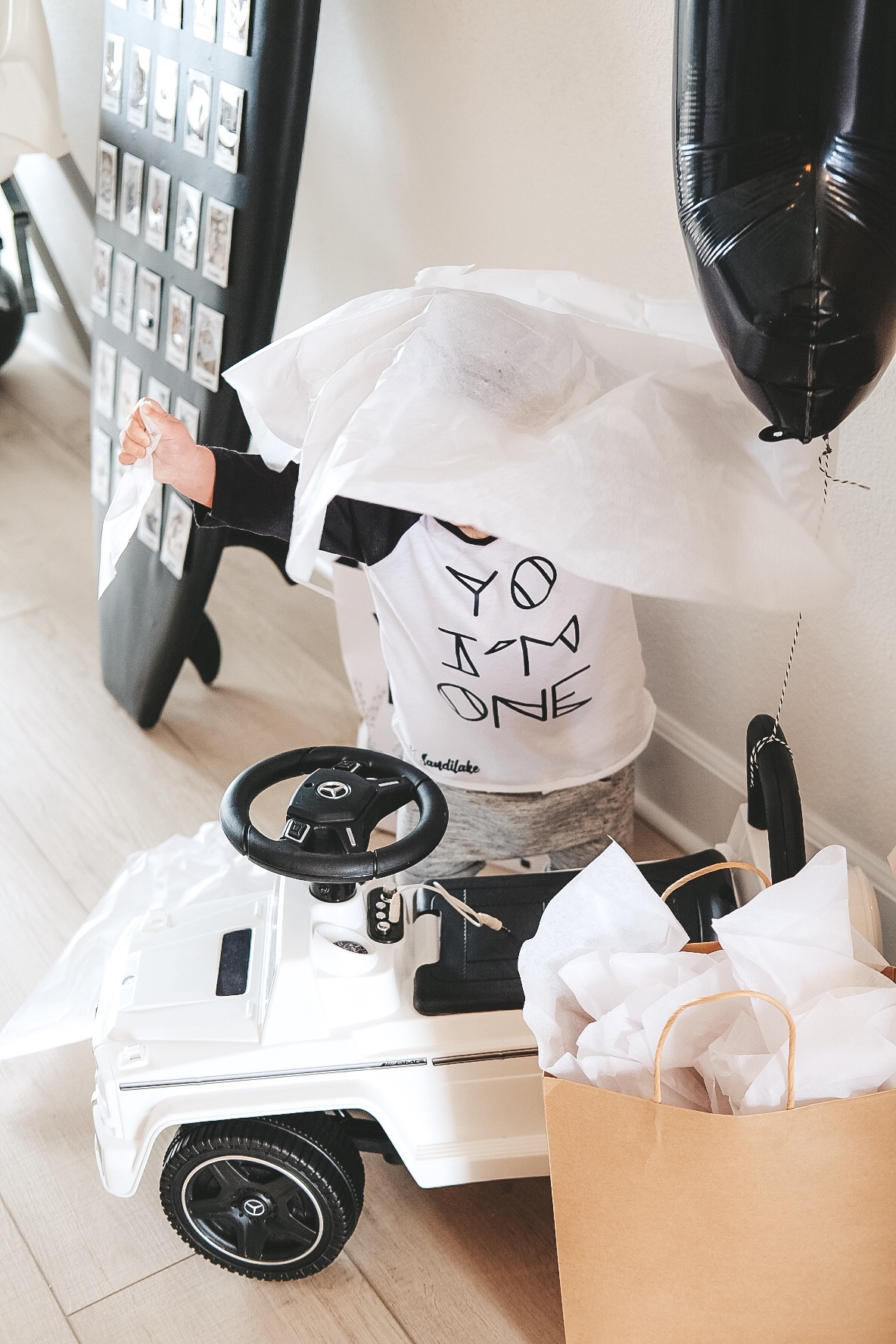 Modern surfer theme birthday party.  Black and white birthday party.  Baby boy frist birthday party. White G Wagon ride along car for 1 year old birthday gift. Yo I'm One shirt for babies first bday.