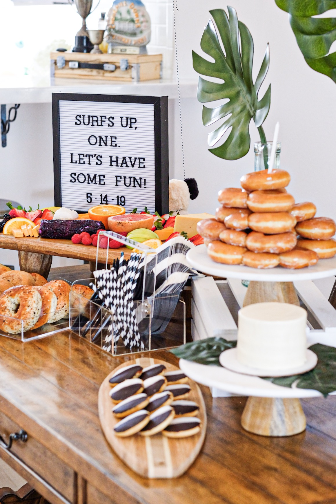 Modern surfer theme first birthday party.  Black and white boy birthday decor.  Krispy Kreme donut cake. Surfboard cheese board.