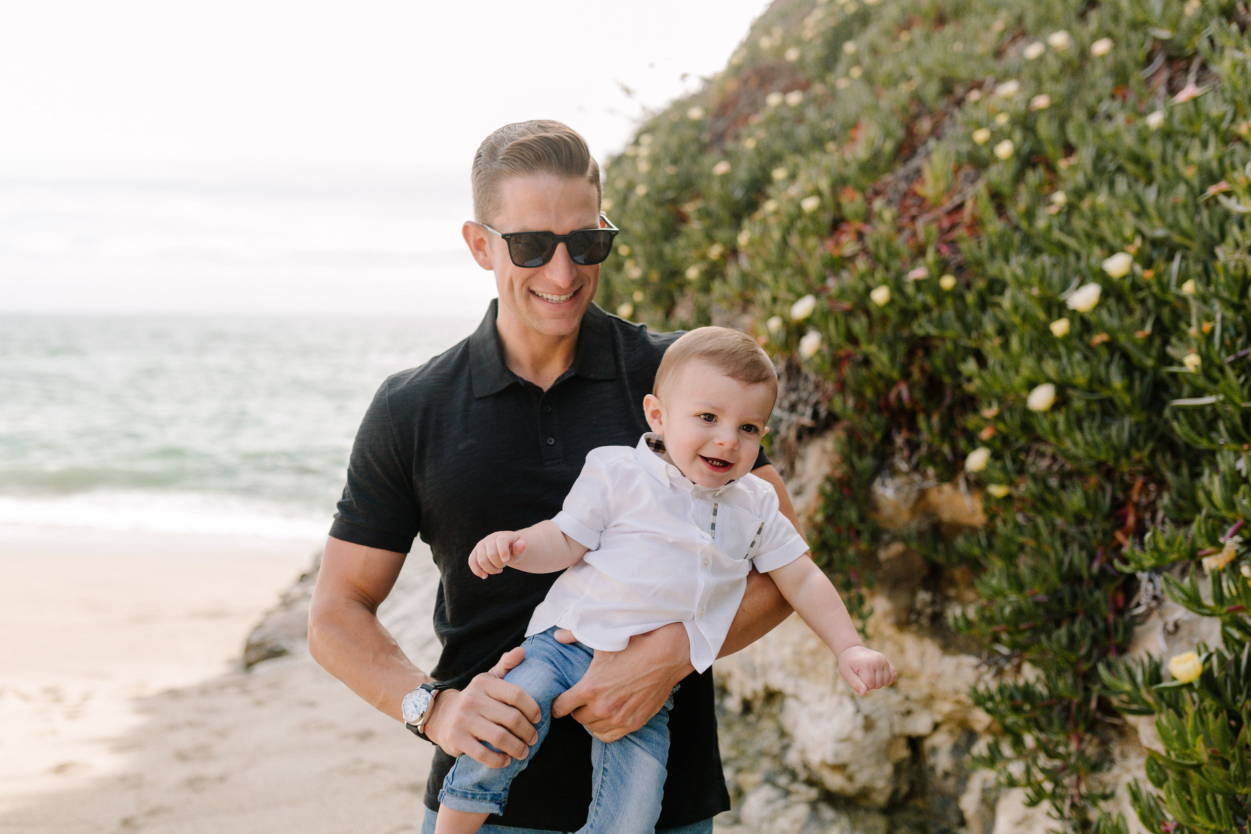 Jones family photos on the beach.  Laguna Beach photos at Table Rock Beach.  Black and white outfits for family photos.  One year old birthday photo shoot.  Baby Burberry shirt.
