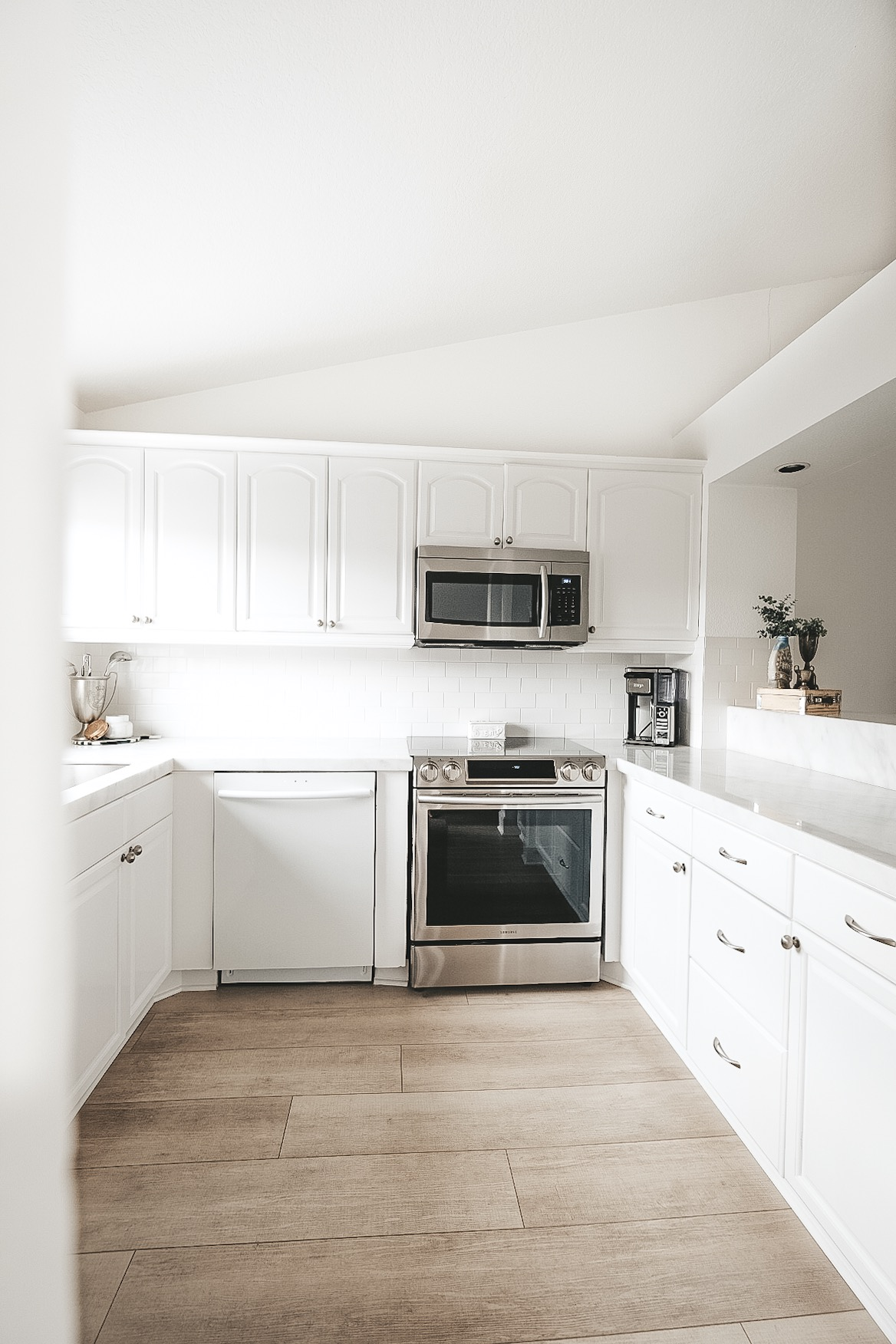Pros and cons of marble countertops in kitchens and bathrooms.  White kitchen with marble countertops and silver hardware.  Light wood flooring.  Light wood LVP floors.