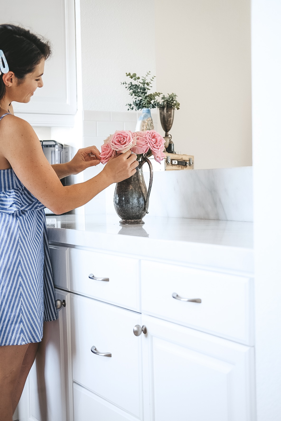 Pros and cons of marble countertops in kitchens and bathrooms.  White kitchen with marble countertops and silver hardware.  Light wood flooring.  Light wood LVP floors. Carrera marble kitchen. White cabinets.