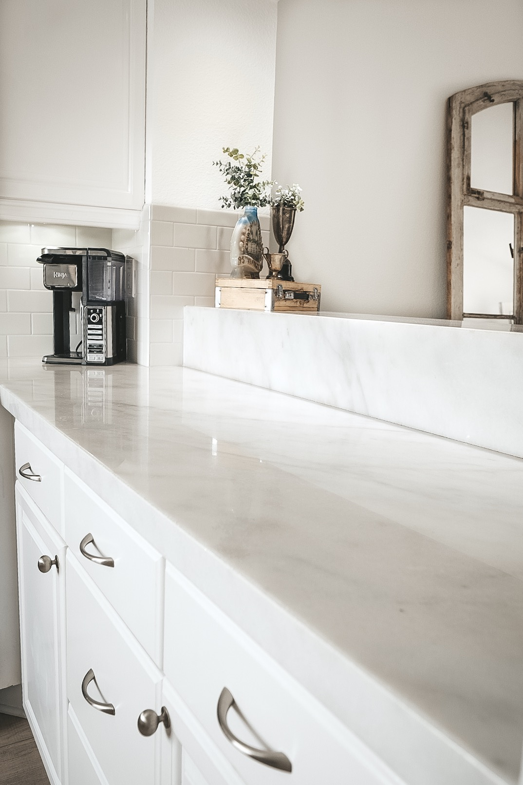 Pros and cons of marble countertops in kitchens and bathrooms.  White kitchen with marble countertops and silver hardware.  Light wood flooring.  Light wood LVP floors. Carrera marble kitchen.