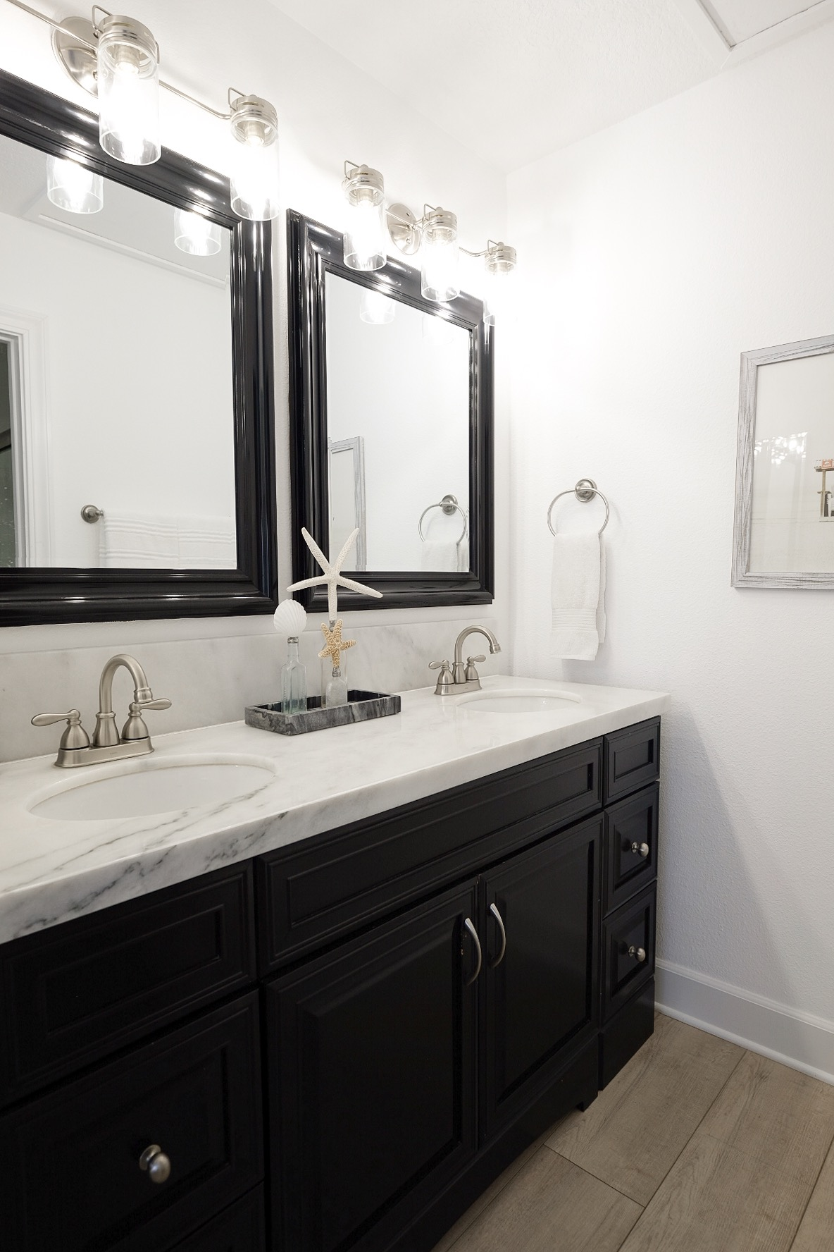 Pros and cons of marble countertops in kitchens and bathrooms.  White kitchen with marble countertops and silver hardware.  Light wood flooring.  Light wood LVP floors. Carrera marble kitchen. Black and white bathroom with light LVP hard wood floors.