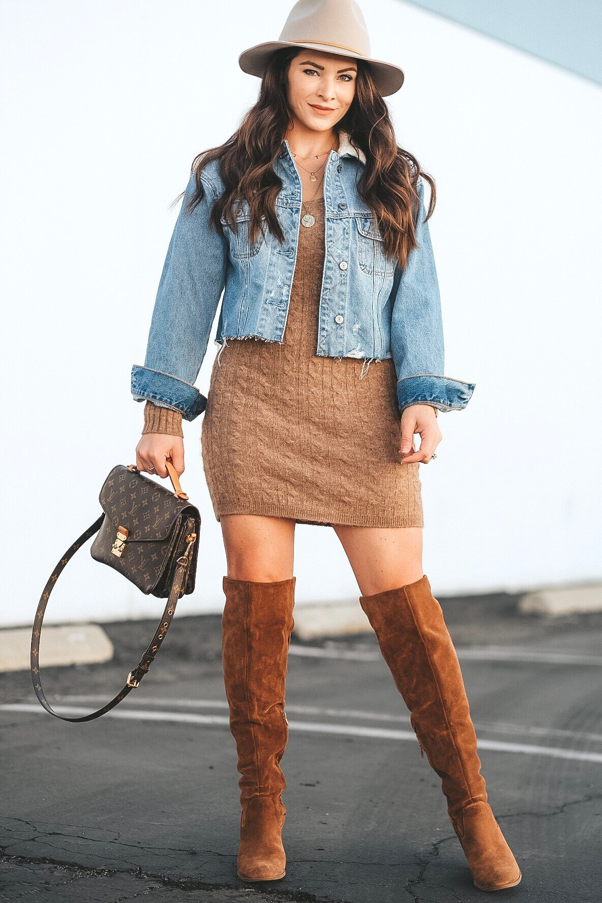 Affordable sweater dresses for fall.  Tan sweater dress with brown boots, cropped denim jacket, layered gold necklaces, and a Louis Vuitton Metis Pochette.