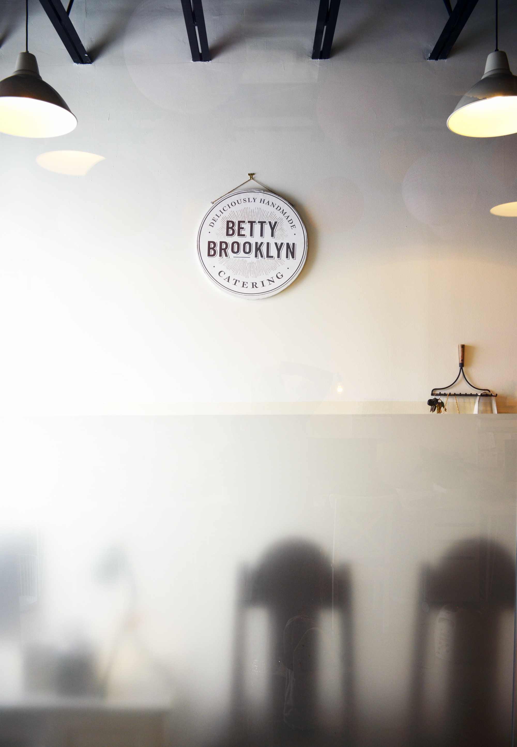 This is the view clients see as they immediately enter to the left - it is Betty's office. The Betty Brooklyn Catering logo and sign is the focal point of that wall    | Betty Brooklyn Catering Co. | Photography by: Lauren L Caron © 2015.