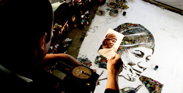 Muniz working on a trash portrait from a platform above