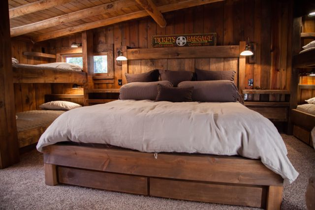 The Bunk Room. All the beds and doors were hand-crafted by our master carpenters. The custom queen size bed in the center has drawers underneath for storage. And floating built-in side tables to provide storage without crowding floor space.