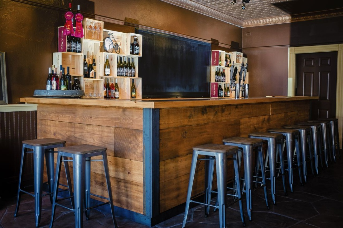 Custom bar with lots of wood to warm up the space and raw steel finishes.