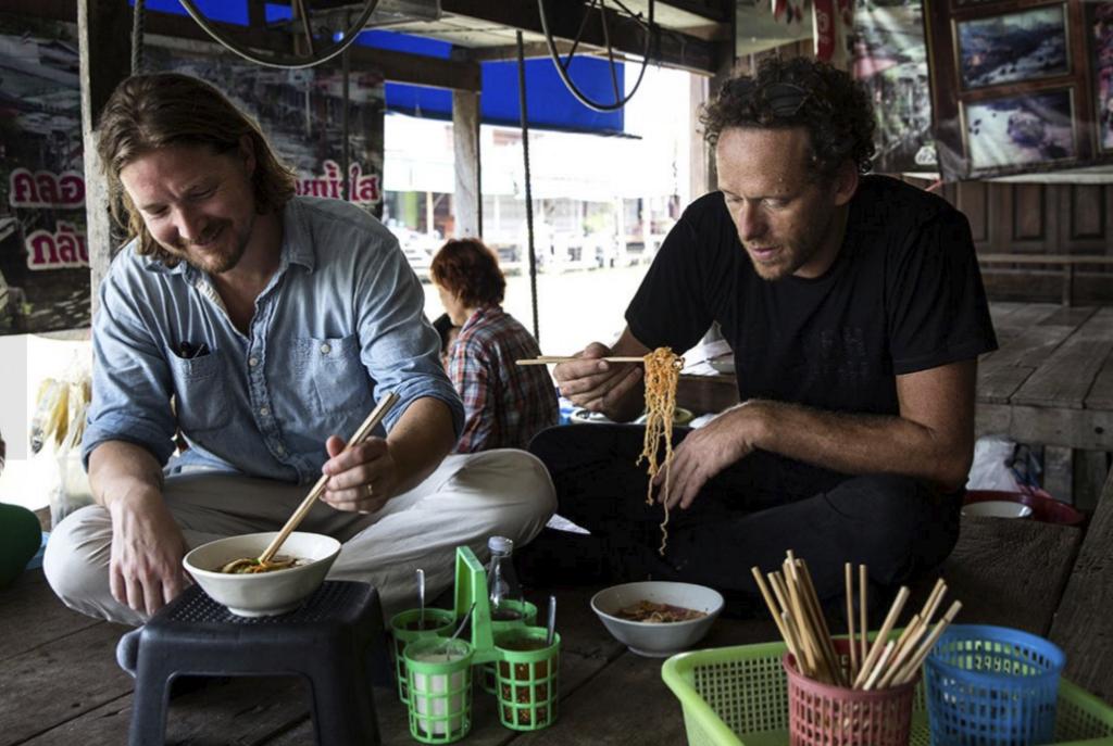Justin Guilbert (left) and Douglas Riboud eating noodle soup at Wat Prasat Sit floating market.