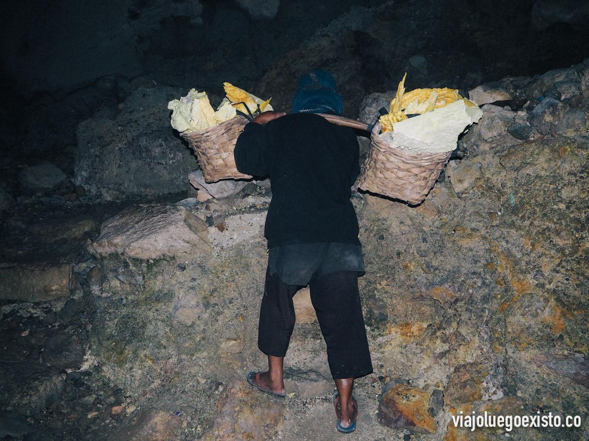 Minero con 2 cestas de azufre entre un tronco de bambú