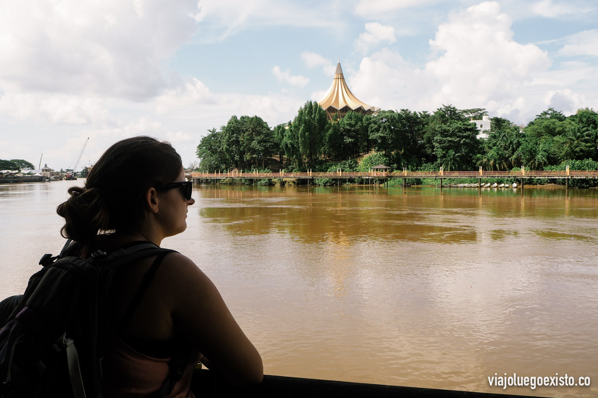 Tam admirando el río Sarawak, con la oficina del gobierno local de fondo