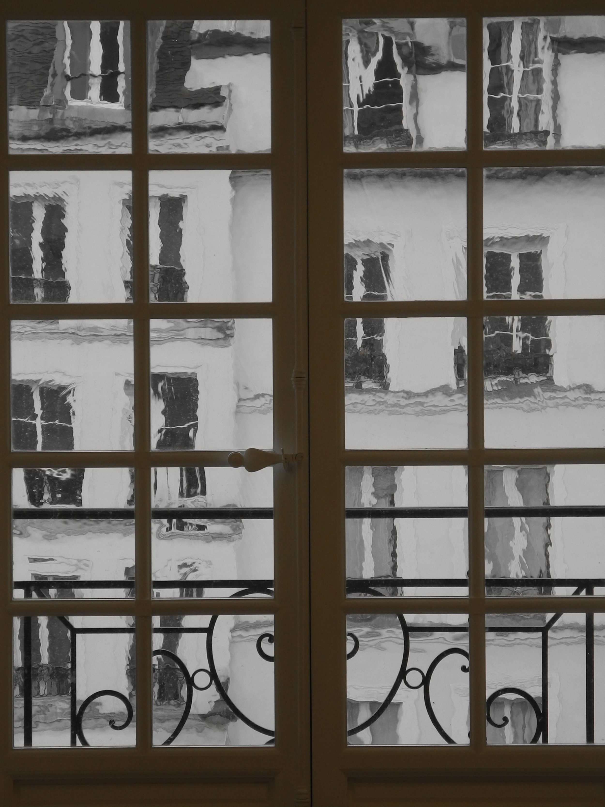 A view into the garden from the wavy glass of the Mansion's antique windows.