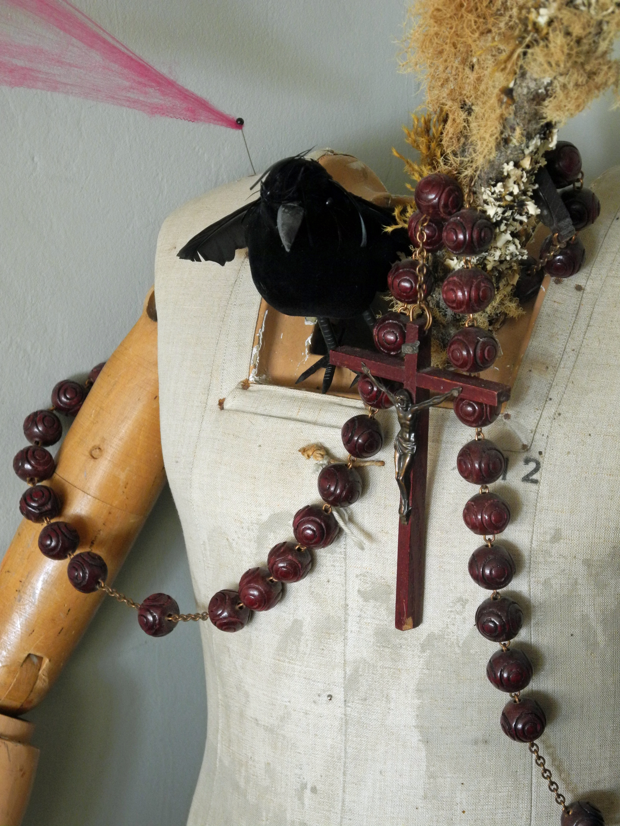 An antique French mannequin turned creepy with a rosary, crow and moss.