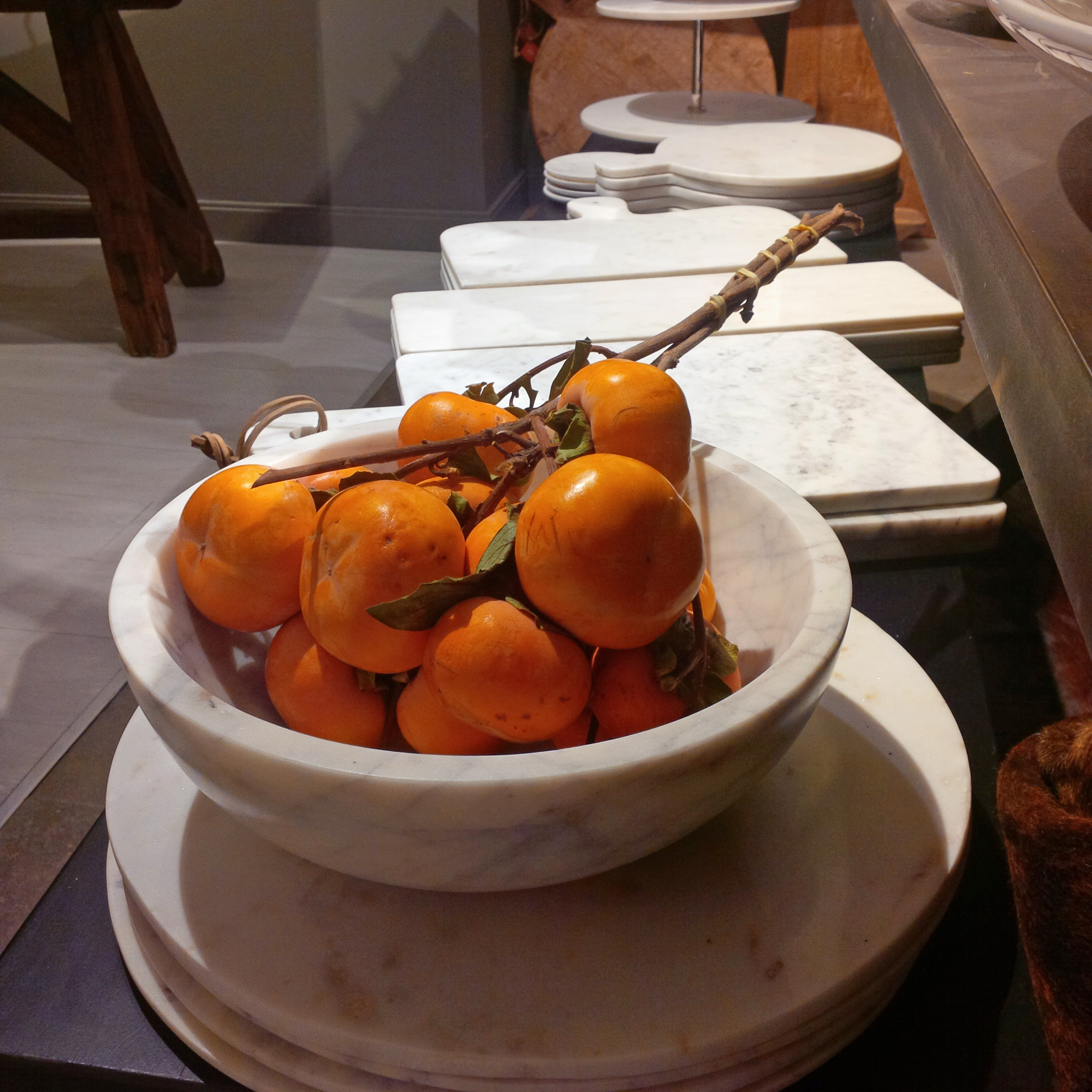 Marble platters with orange persimmons are a simple chic Holiday table setting.