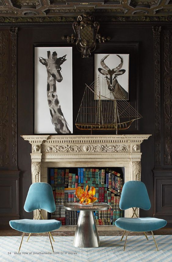 These blue chairs contrasted against the dark brown wall are like Spring emerging from Winter...oh, and those books in the fireplace, pure genius. {via  Jonathan Adler }
