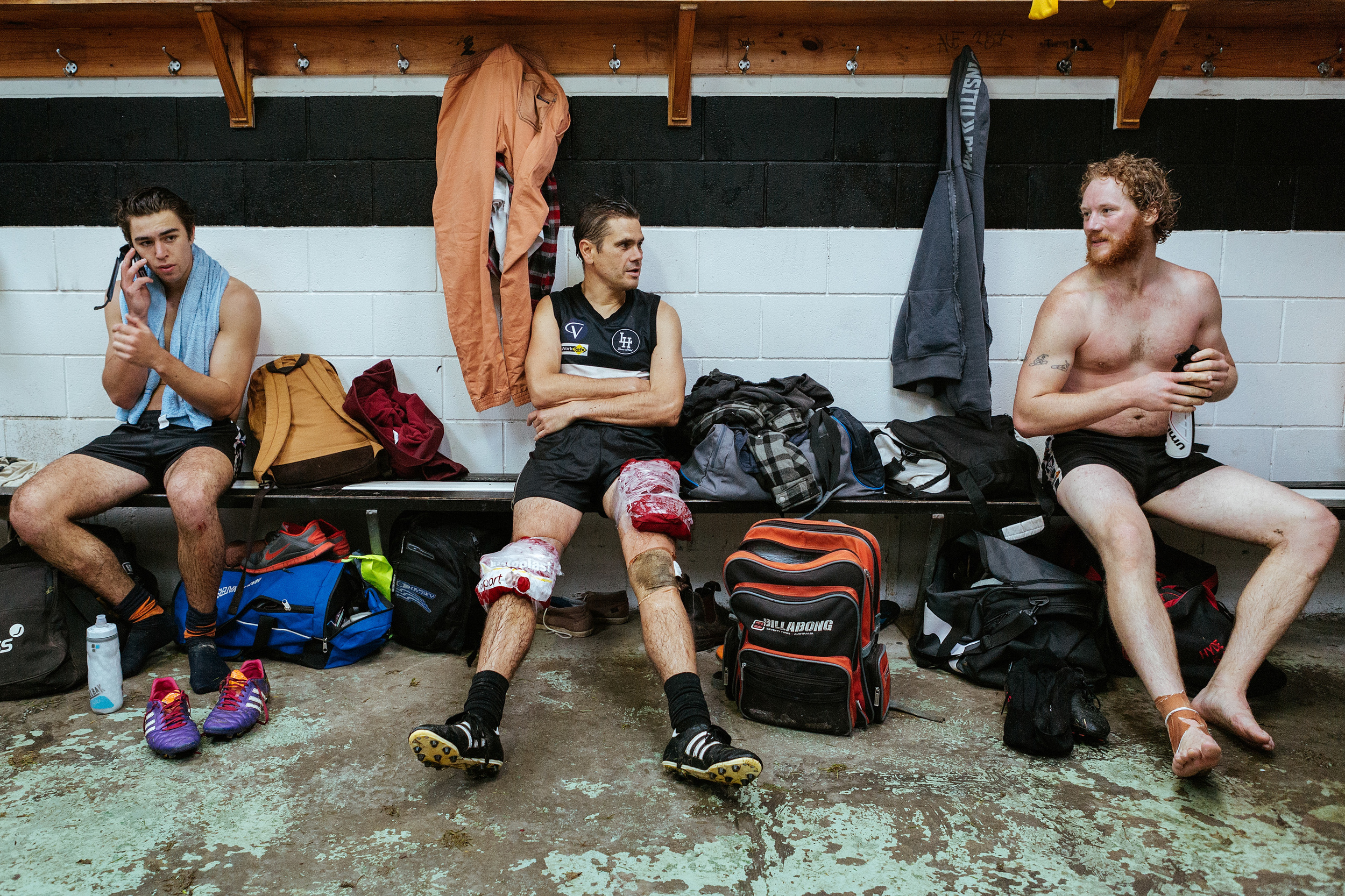 Players from the Lorne Football Club reserves side in the change room post match get their injuries patched up and discuss the match.