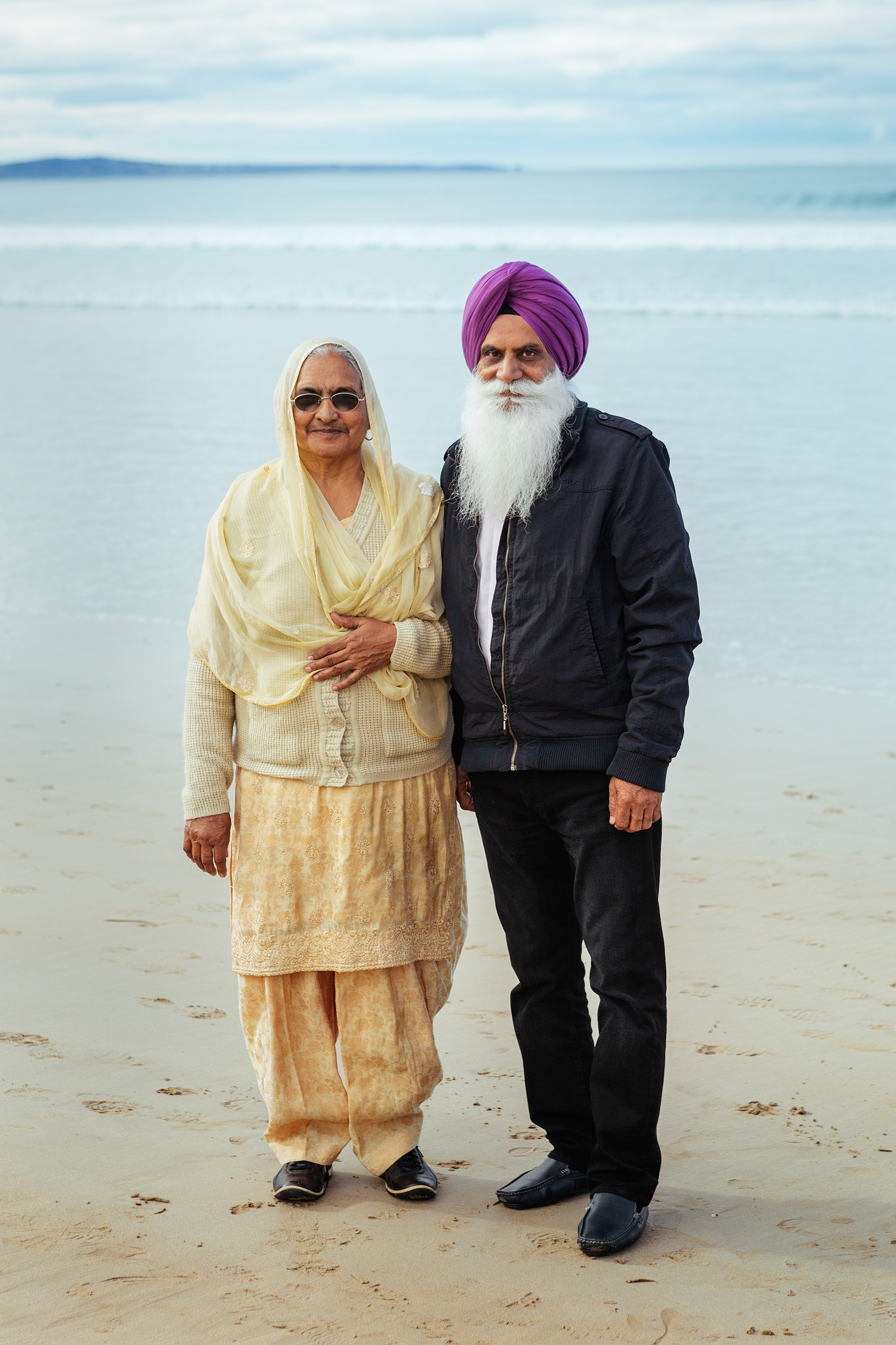 An elderly couple visiting their family from India pose for a photo on the beach.  He explains how worried he was about how they would be received in Australia and how impressed he has been with the welcoming and warmth towards them.