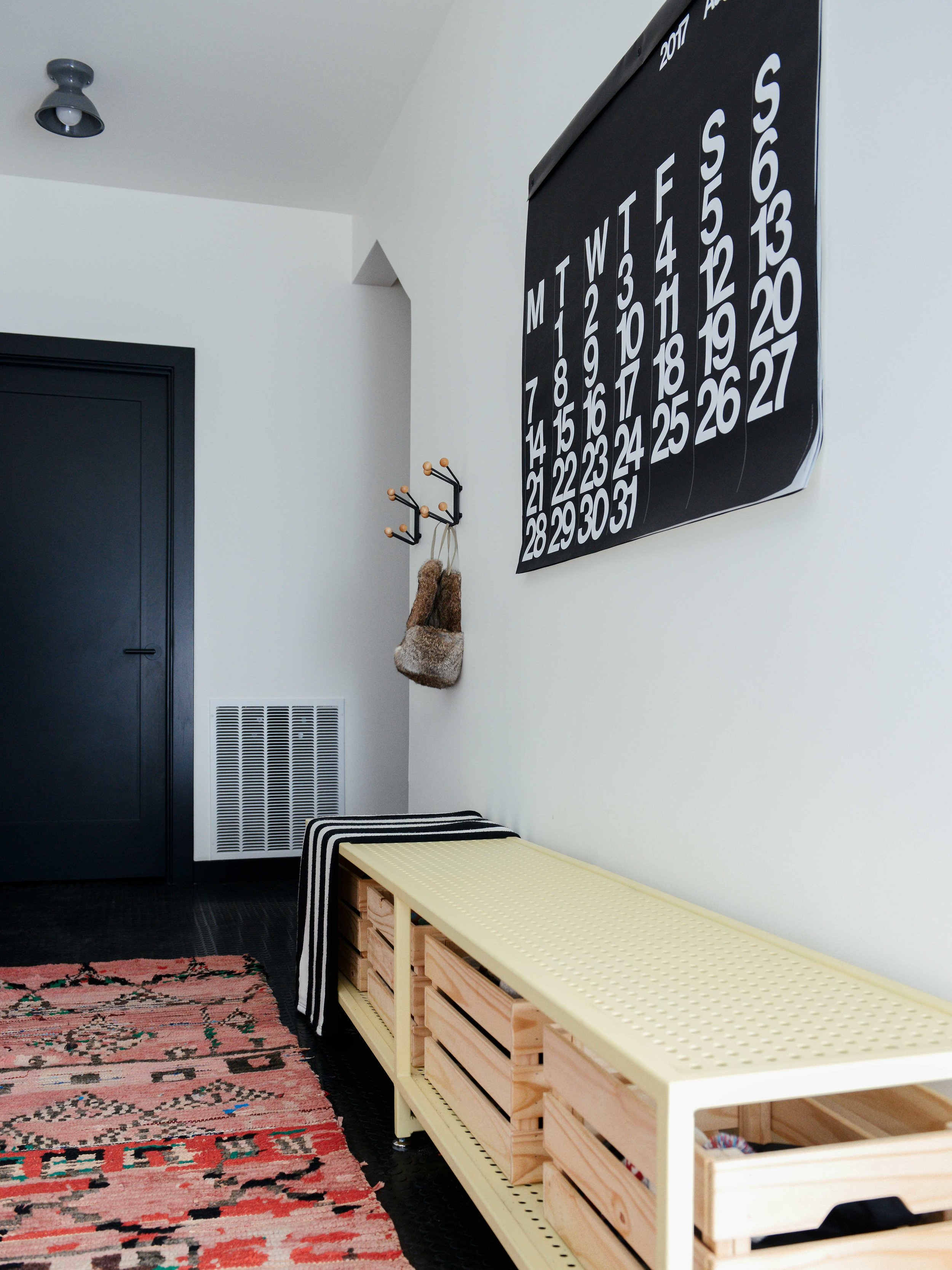Above: A custom steel perf banana yellow bench for taking off snowy boots rests on a black rubber floor. The rug is by  Kat + Maouche  and the surface mount is from  Schoolhouse Electric .